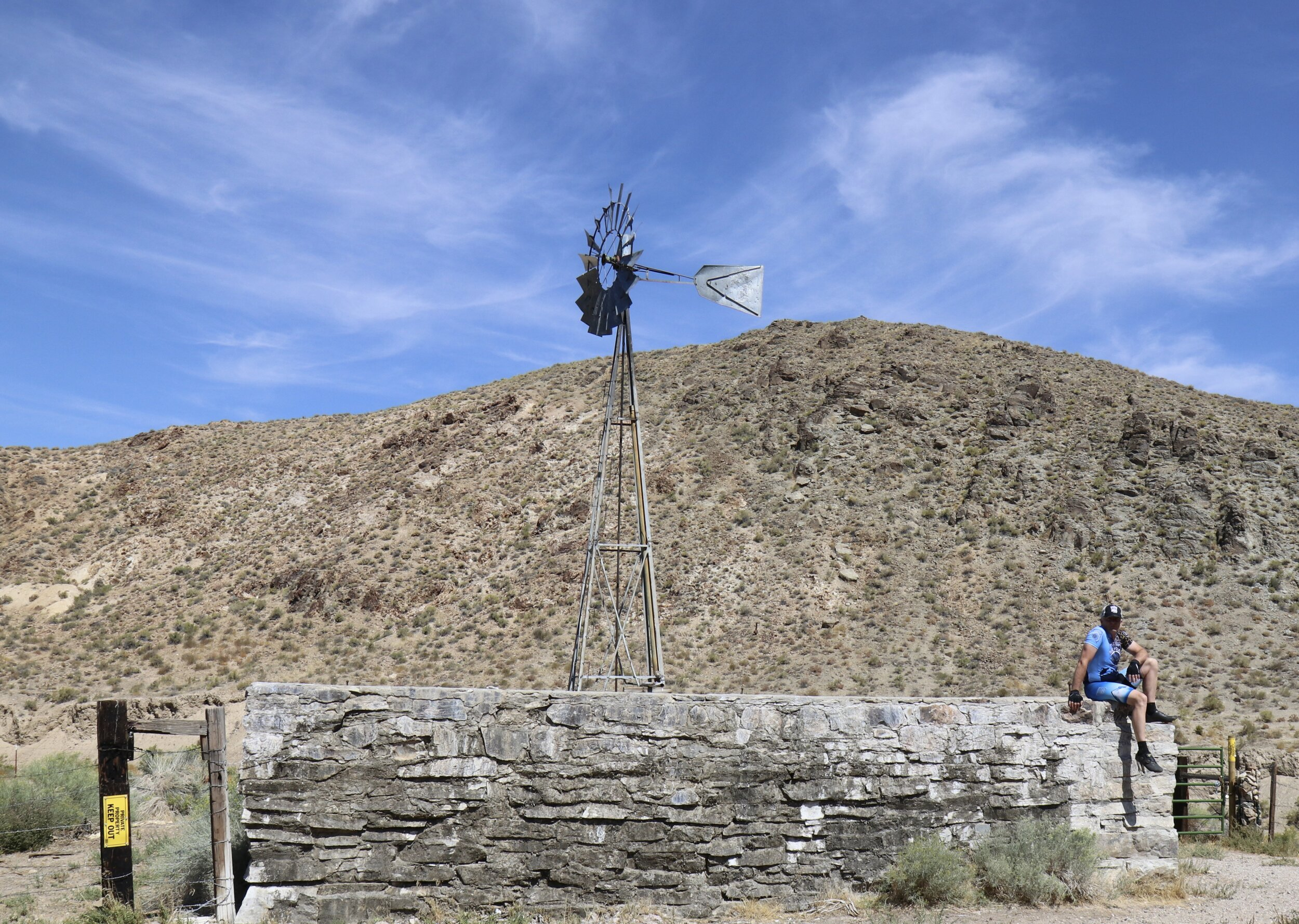 Me sitting on the edge of a huge water retention basin filled by the windmill on the Pony Express Route across Nevada.