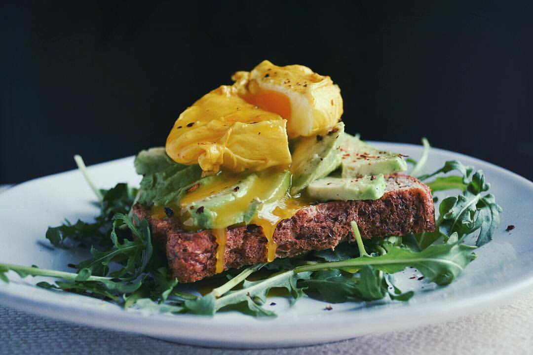 Avocado toast with a turmeric poached egg over a bed of arugula