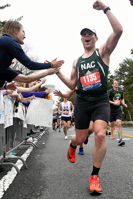 """Jeremy J. Bauer, Ph.D., high-fives spectators in the """"Scream Tunnel"""" near Wellesley College between miles 12-13 of the 2019 Boston Marathon."""