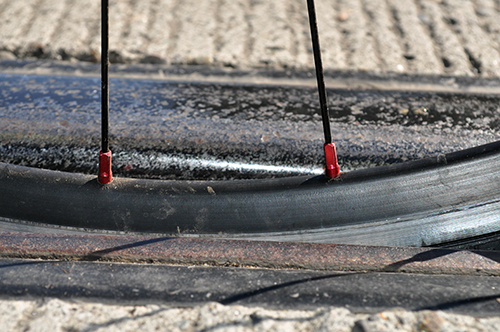 Photograph showing a dangerous condition created when a bicycle tire becomes lodged in the flange gap between a street trolley track and the road surface.