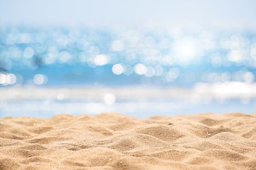 Seascape abstract beach background. blur bokeh light of calm sea and sky. Focus on sand foreground.