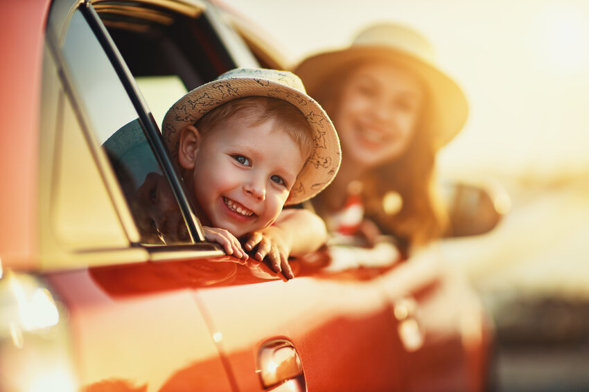 happy family mother and child boy goes to summer travel trip in car