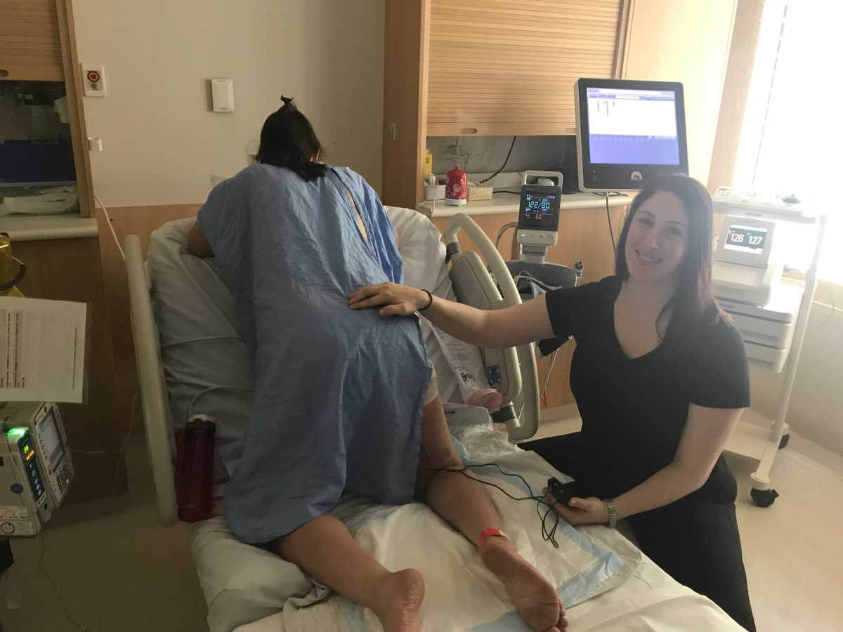 Supporting a birth doula client during established labour with massage and a tens machine
