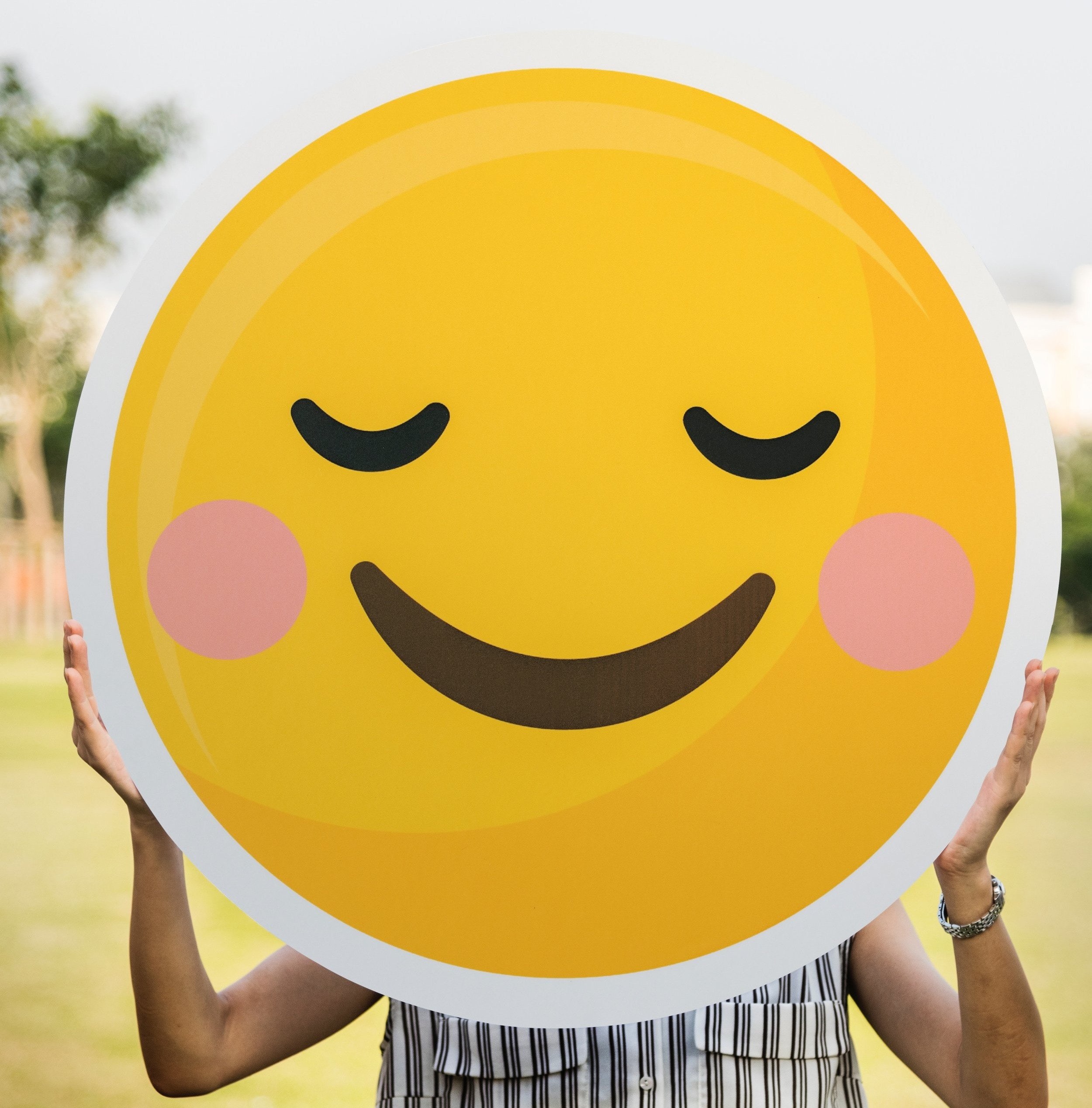 woman-holding-smiley-face.jpg