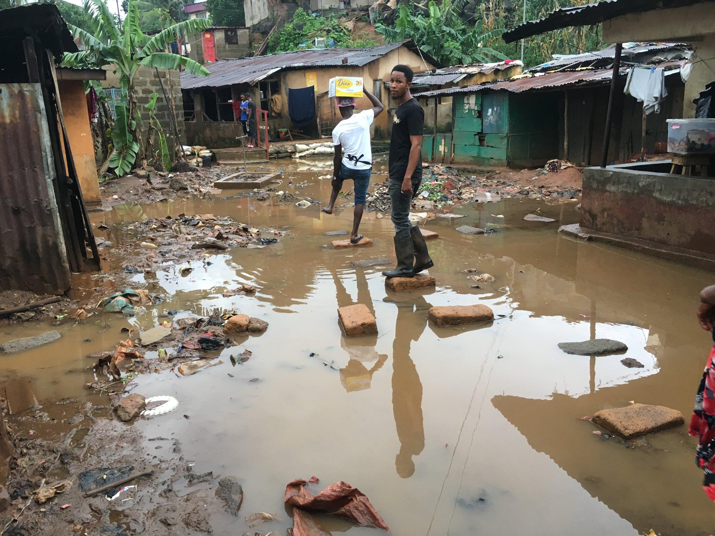 Joseph standing in Culvert community, Freetown