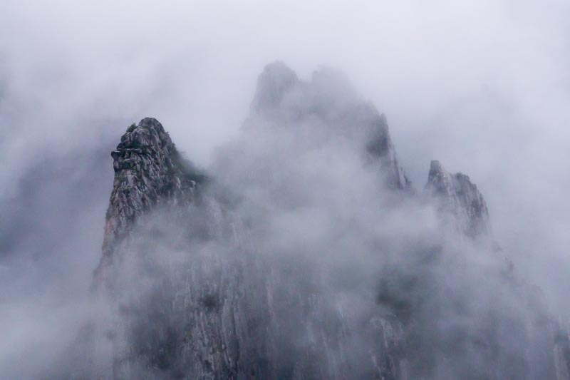 The El Potrero Chico summits covered with low clouds on a cold rainy day.
