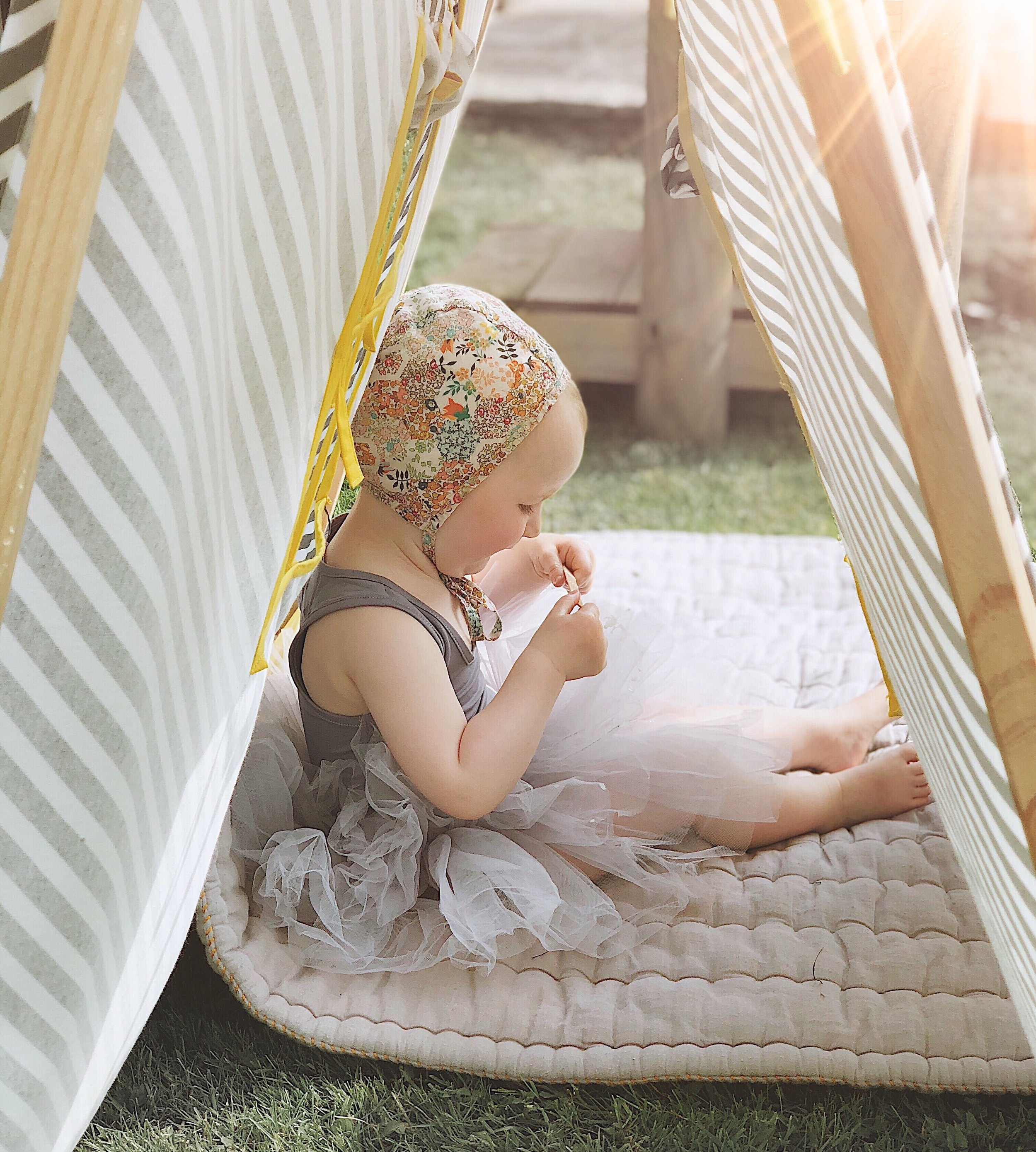 Wearing tutu from Plum NYC, blanket by Camomile London and play tent by Ferm Living Kids.