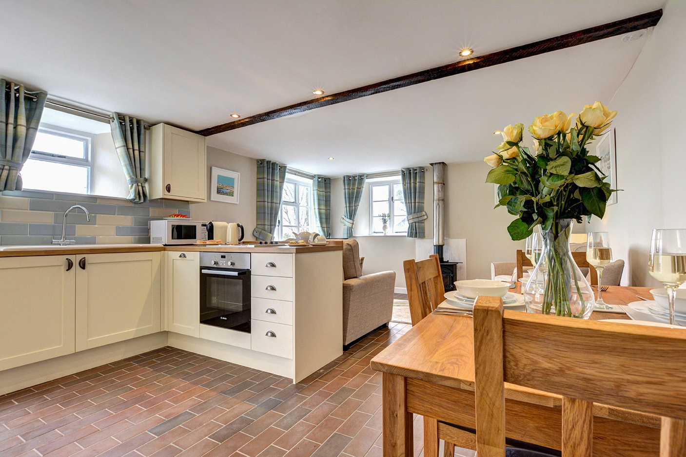The dining area and kitchen of Butterwell luxury self catering converted barn holiday cottage at Penrose Burden in North Cornwall 01.jpg