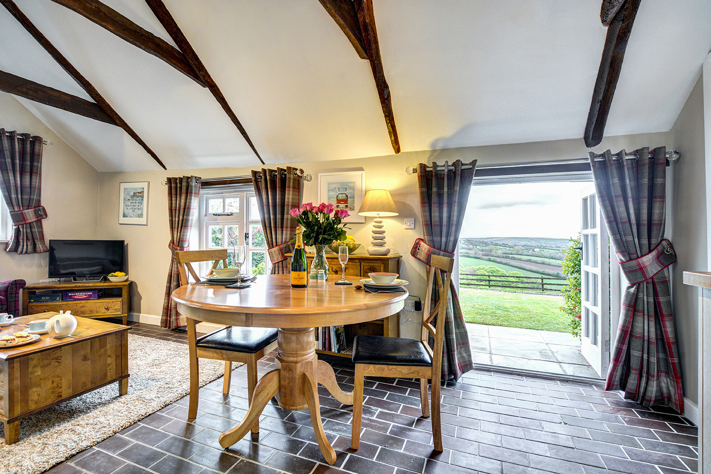 The lounge and dining area looking out the patio doors of The Linney self catering cottage converted barn at Penrose Burden holiday cottages in Cornwall.jpg