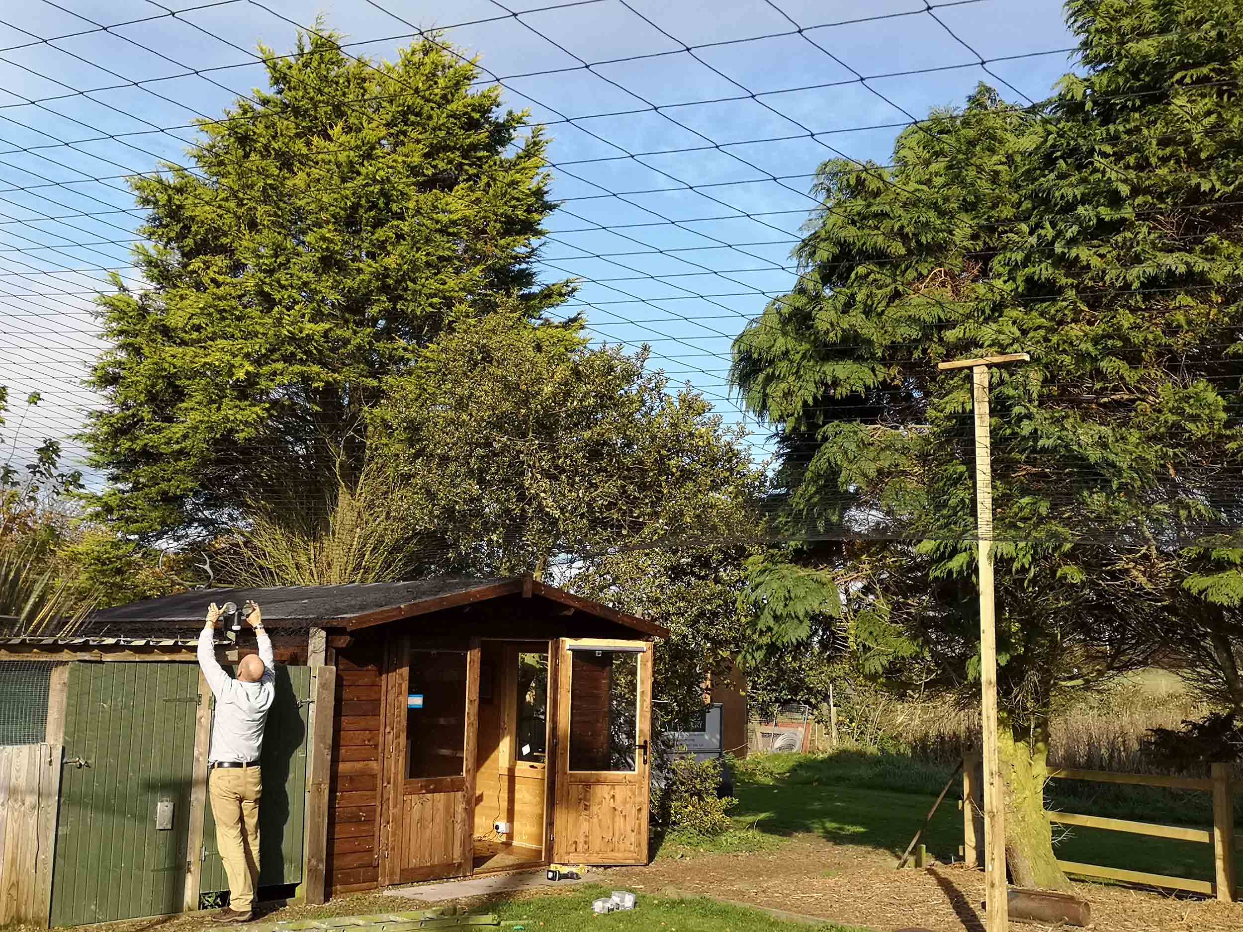 Steve putting up netting over the weathering.jpg