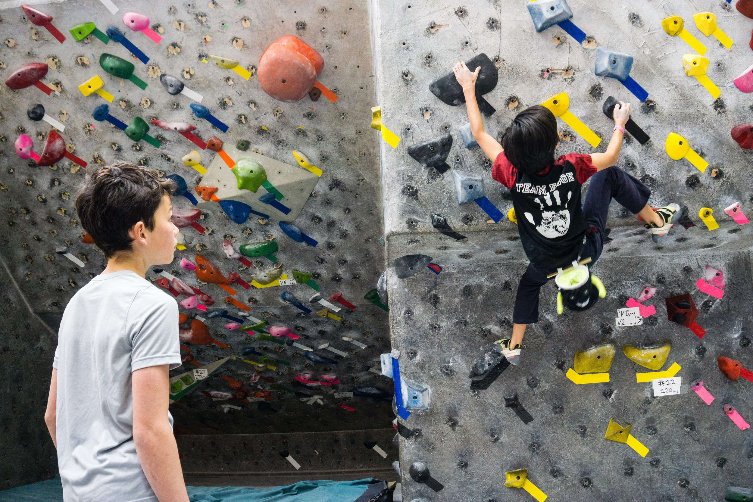 2) A youth climbing competition at Pacific Edge. One student of plastic stares at the other solving one of the problems.
