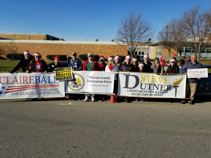 """Mclean County Libertarian Party members march in the Bloomington Christmas Parade on December 4, 2017"""" (Credit: McLean County Libertarian Party)"""