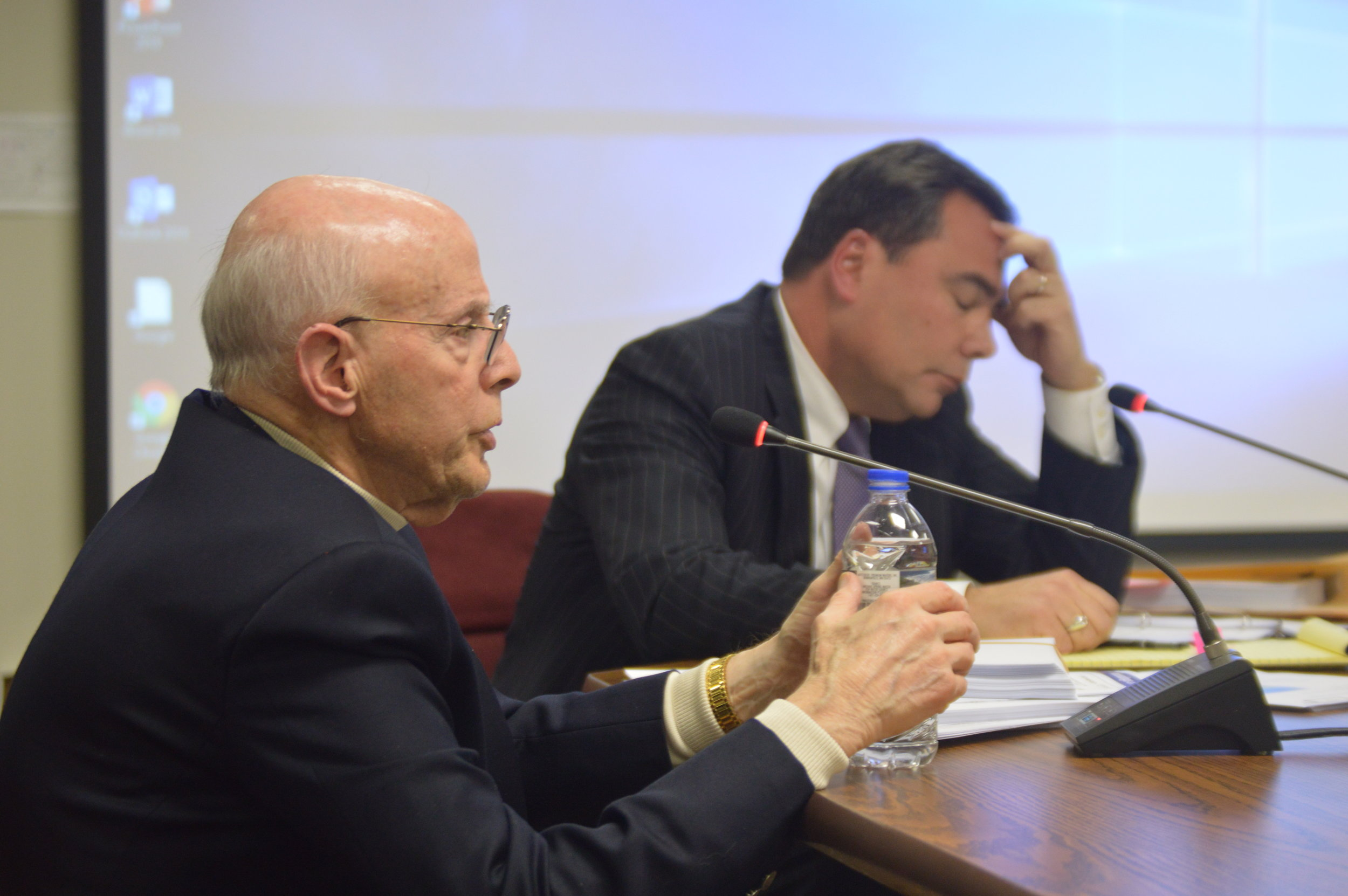 Dr. Phil Schomer, left, testifies before the McLean County Zoning Board of Appeals Wednesday night. Attorney Phil Luetkehans, right, represents residents and property owners opposing the project. (Image Credit: Breanna Grow)