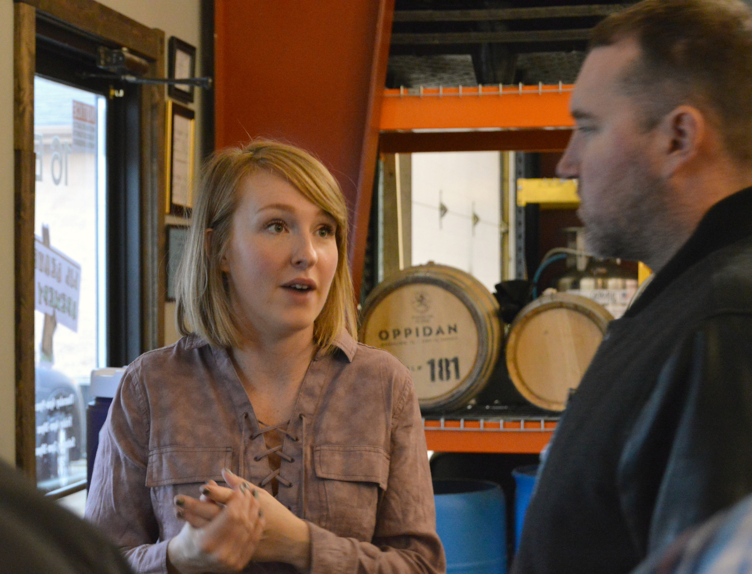 Eclectic Hearts founder Megan Cowie talks with patrons at a pledge party Friday evening at Lil' Beaver Brewery in Bloomington.