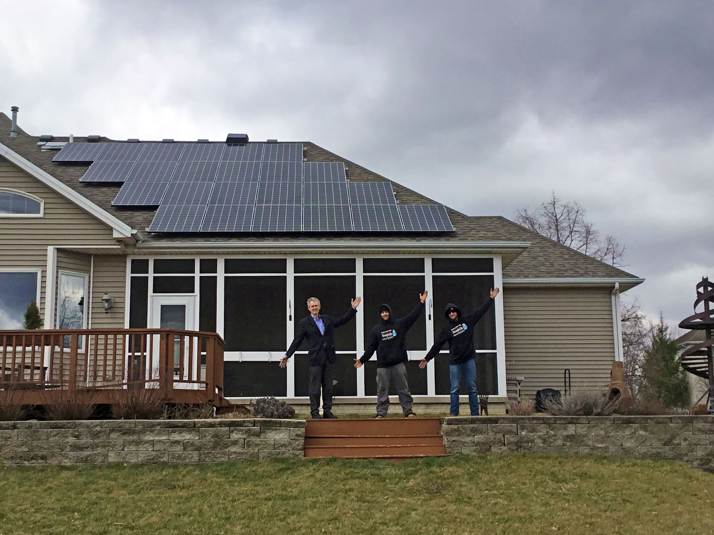 A solar homeowner celebrates with two StraightUp Solar employees on the day his system was installed.(Image credit:StraightUp Solar)