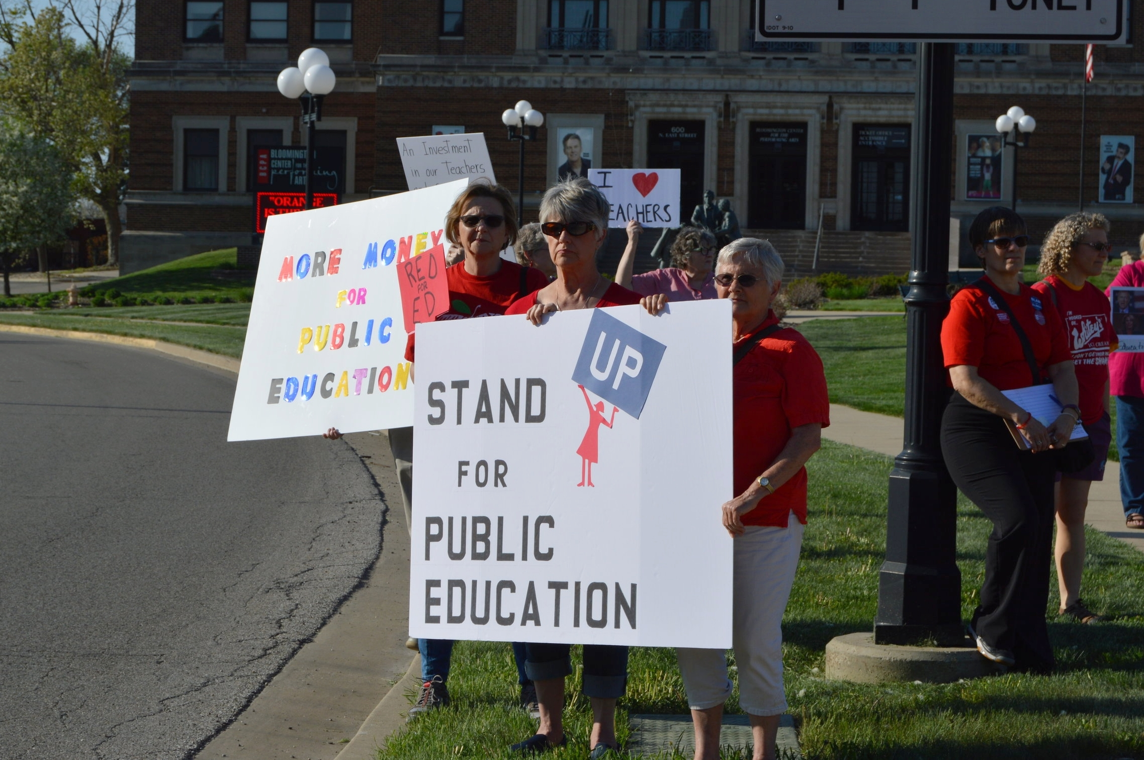 Members of the Stand Up for Social Justice coalition advocate for greater public education funding at a vigil outside the Bloomington Center for Performing Arts Monday. (Photo:Breanna Grow/AdaptBN)
