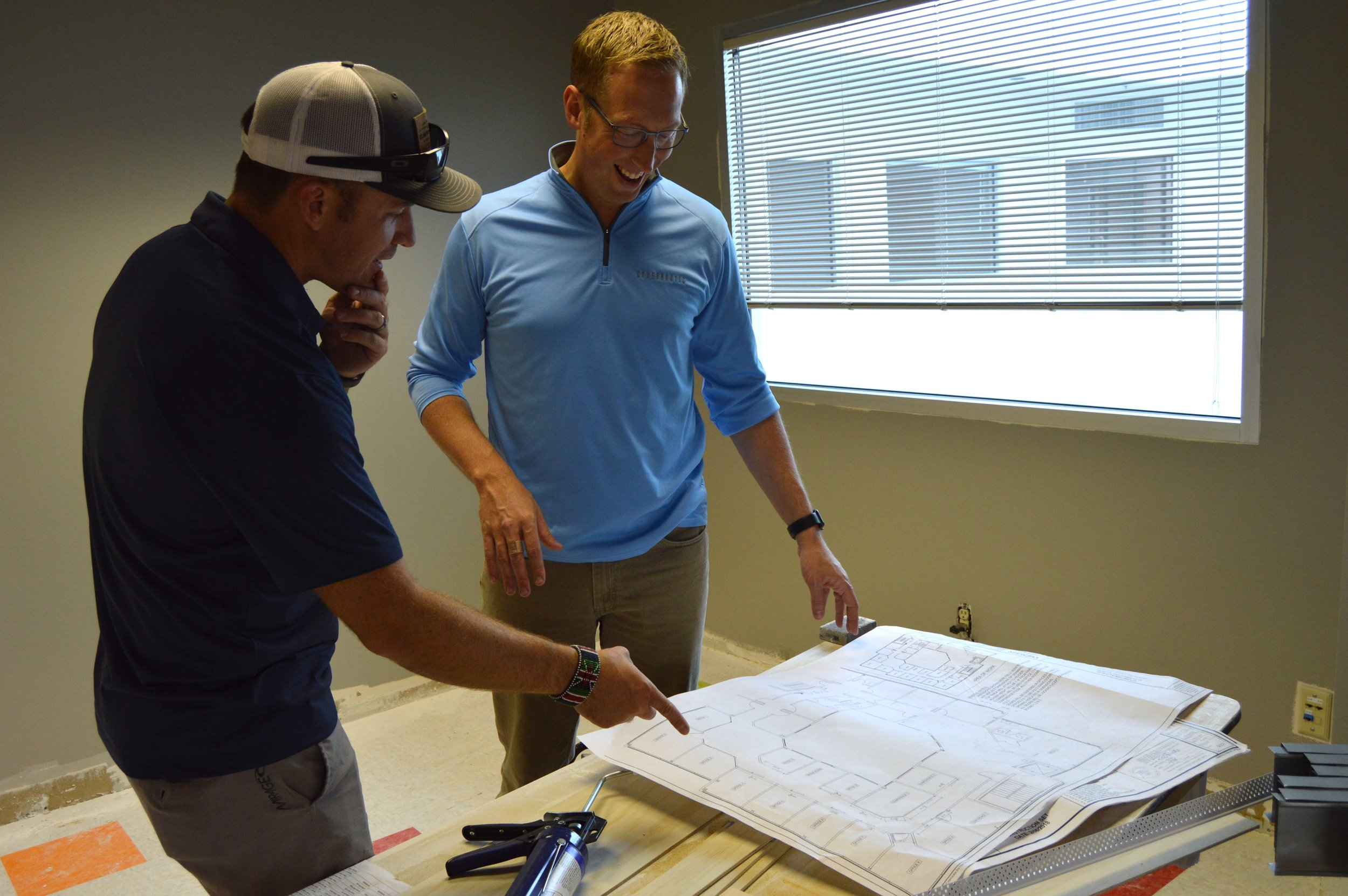 Cybernautic Founder and CEO Chad Parker (Left) and Vice President and Chief Potential Officer Robbie Osenga review renovation plans for their new offices on Empire Street in Bloomington. (Photo: Breanna Grow/AdaptBN)