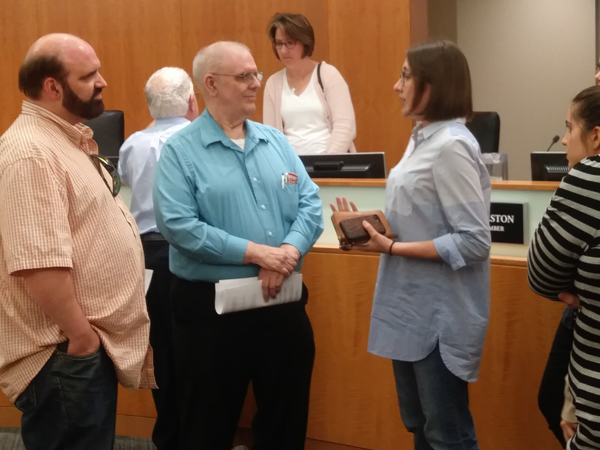 Normal property owners Karl and Charles Sila talk with Illinois State University students after Town Council members approved a multi-family recycling ordinance Monday night. (Photo: Breanna Grow)
