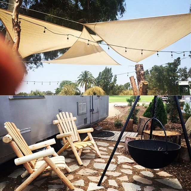 Shade sails tightened up and rustic Adirondack chairs placed around fire pits #getyourstreakon #vintagewinecountryglamping #silverstreaktrailer
