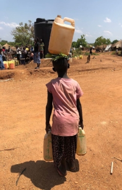 Young girl carrying three jugs of water.