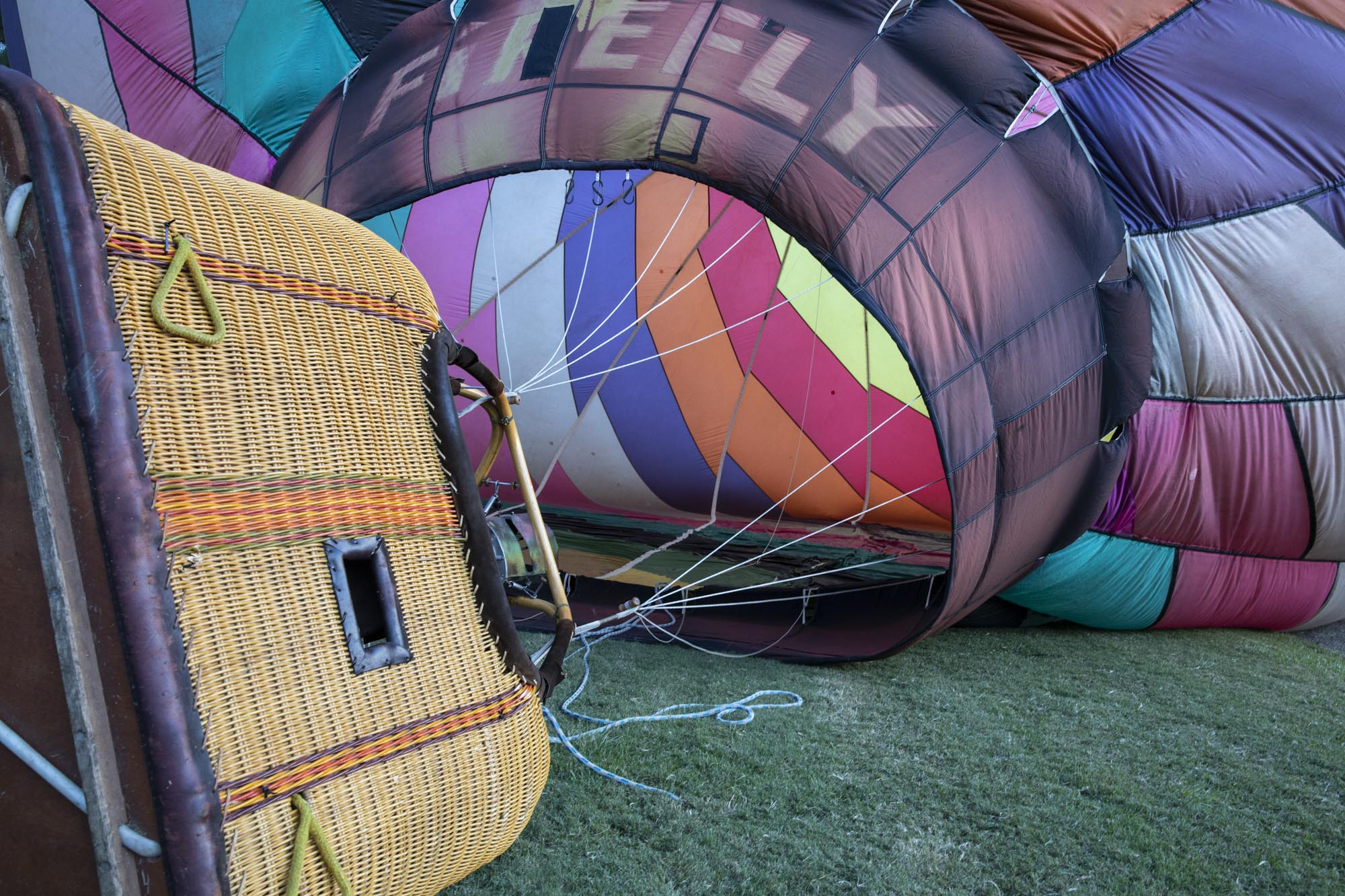 The basket and balloon laying on the ground nearly ready for filling with hot air from the burner.