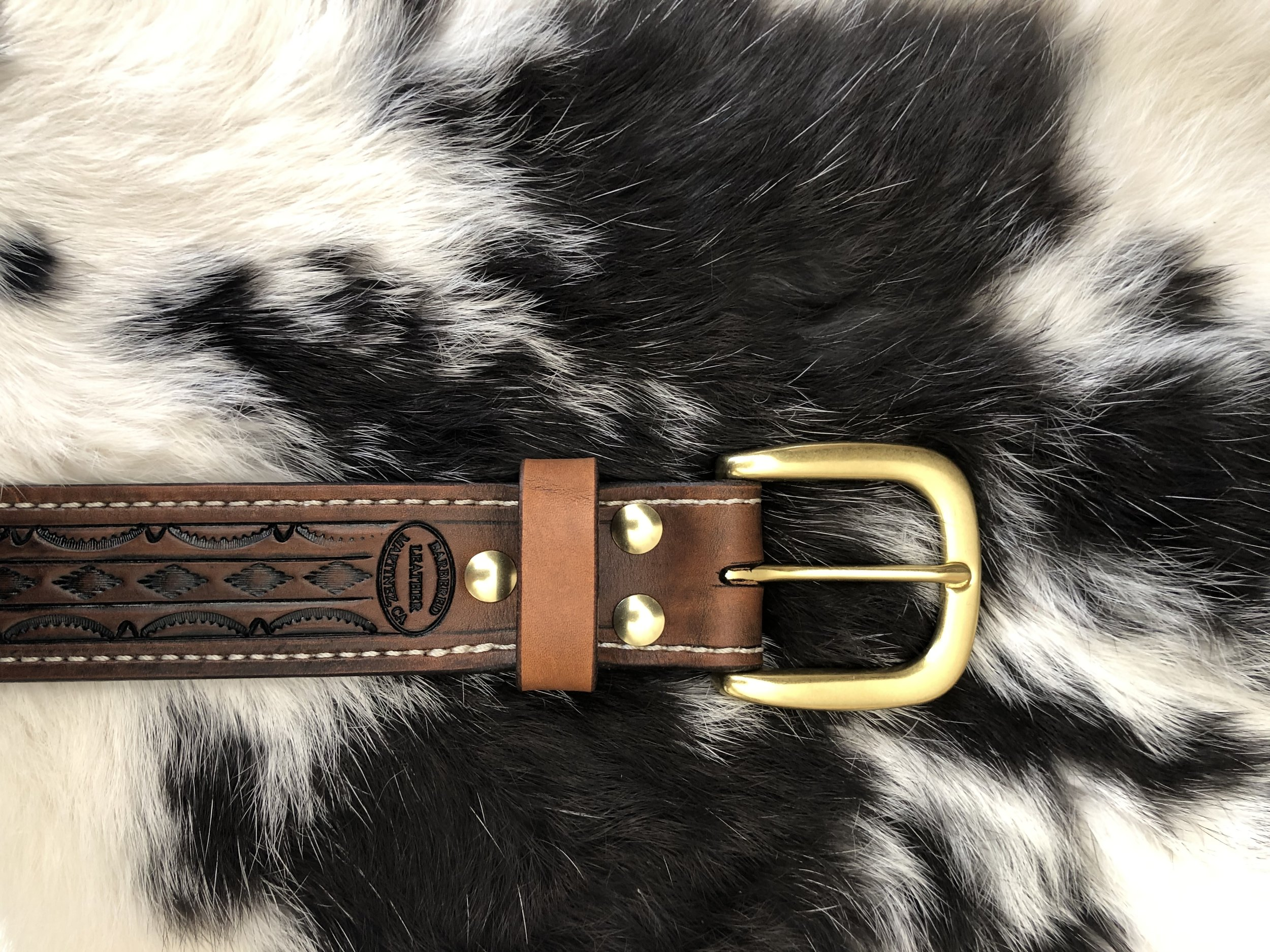 An  Antiqued  premium belt in  Pattern XXX  with a  White Stitch  and a  Heel Bar Round buckle in Brass .  Chicago Screw in Brass  as the fastener.