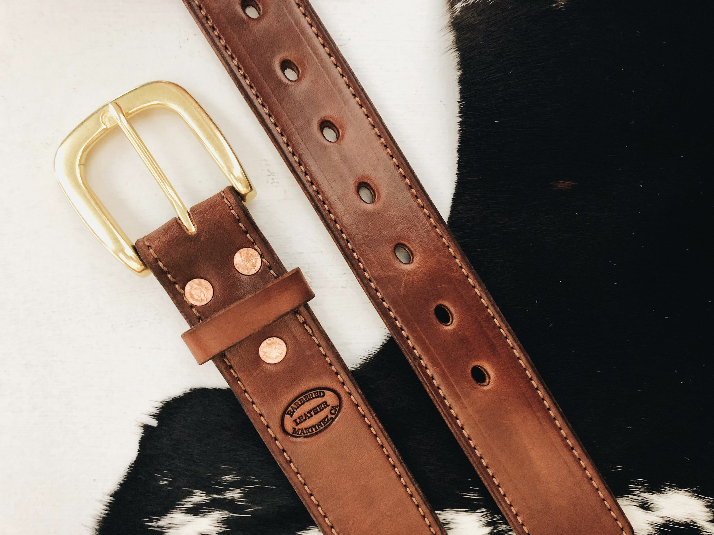 A  Brown  standard belt with a  Brown Stitch  and a  Heel Bar Round buckle in Brass .  Rivets  as the fastener.