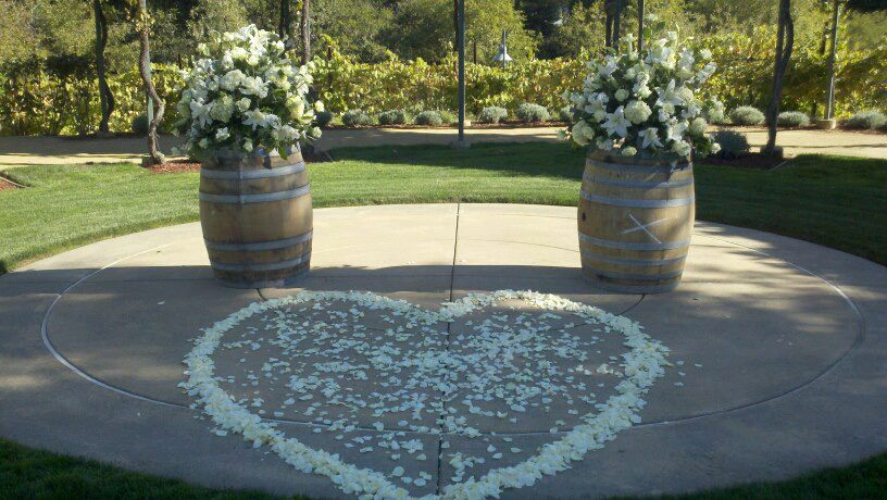 Rose Petals form heart for ceremony. Wine barrel toppers in whites, ivory and greens, Sonoma County wedding, Wine Barrel flowers wedding ceremony