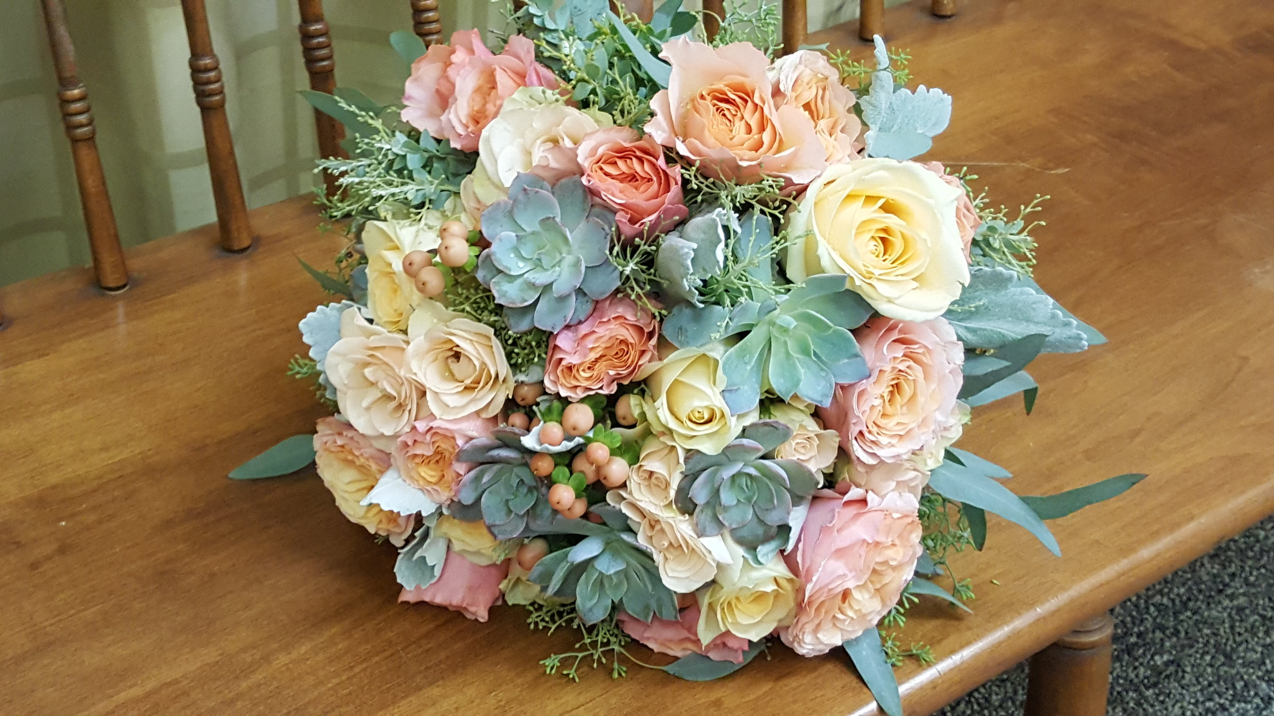 Flowers include roses, ranunculus, succulents and hypericum berries, Apricot, blush and sage green bridal bouquet