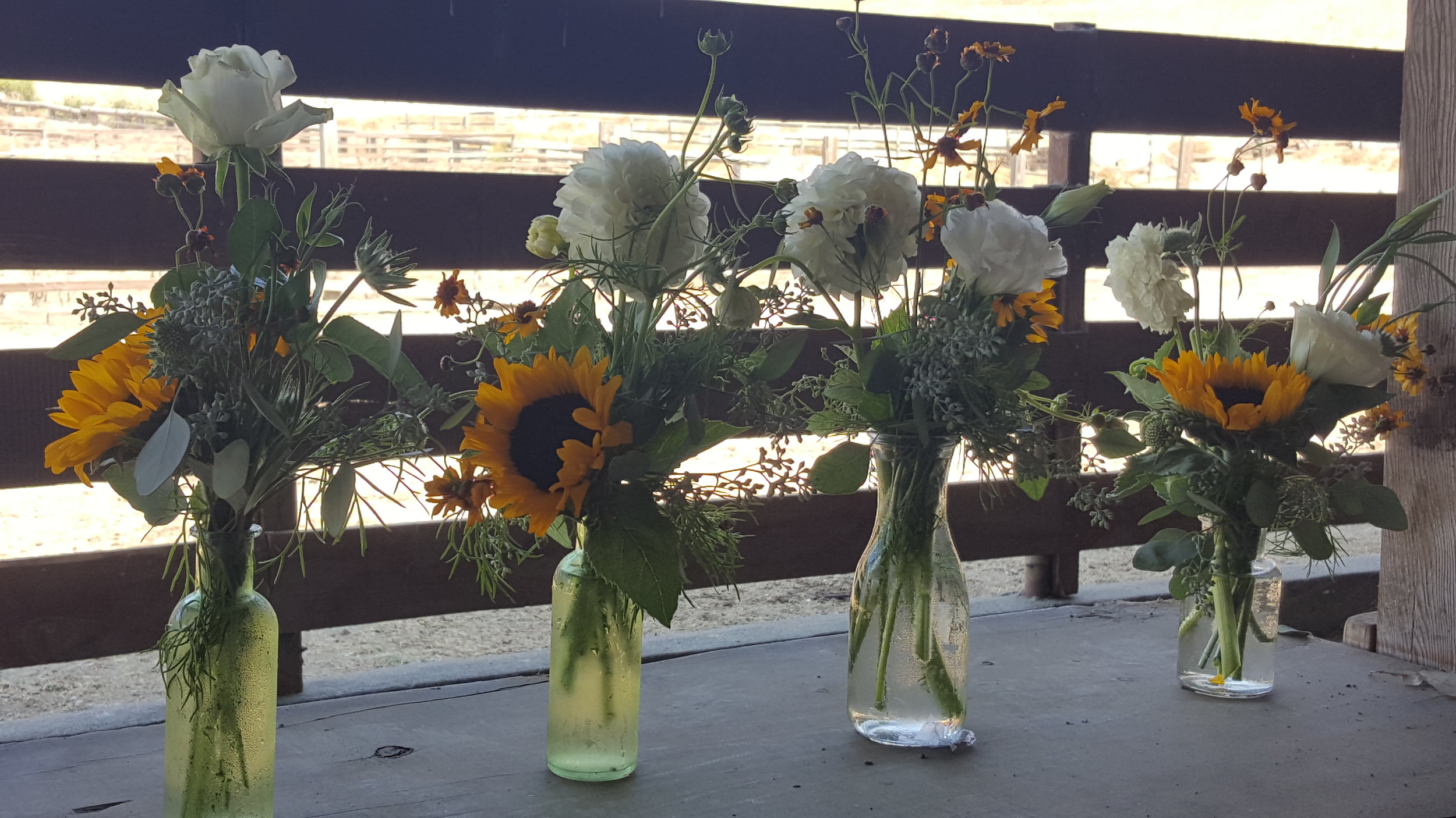 Milk bottle vases with local wild flowers line farm tables for rustic barn wedding centerpiece flowers.