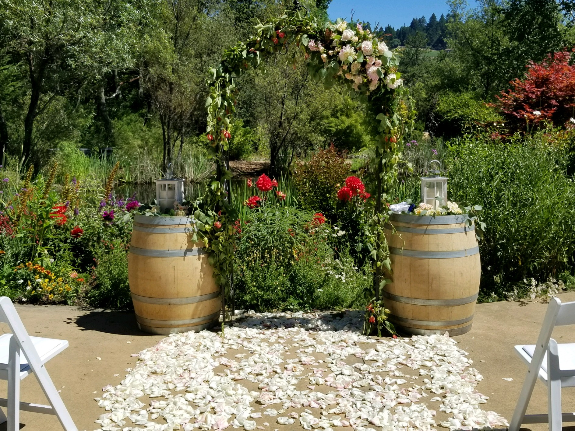 Hans Fahden wedding ceremony, rustic arch flowing with greens and flowers. Wine barrel toppers include large lanterns with floral wreath. Petals mark the aisle for the bride and groom.