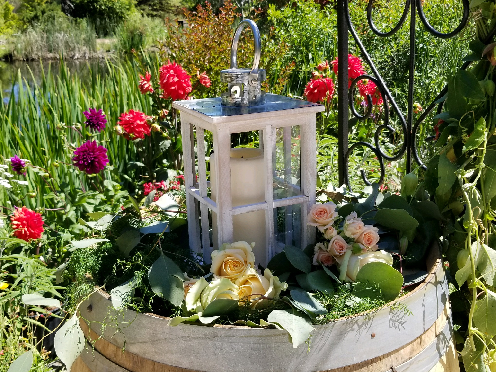 Hans Fahden wedding ceremony by the pond. Wine barrel topper featuring white rustic lantern and romantic flowers and greens.