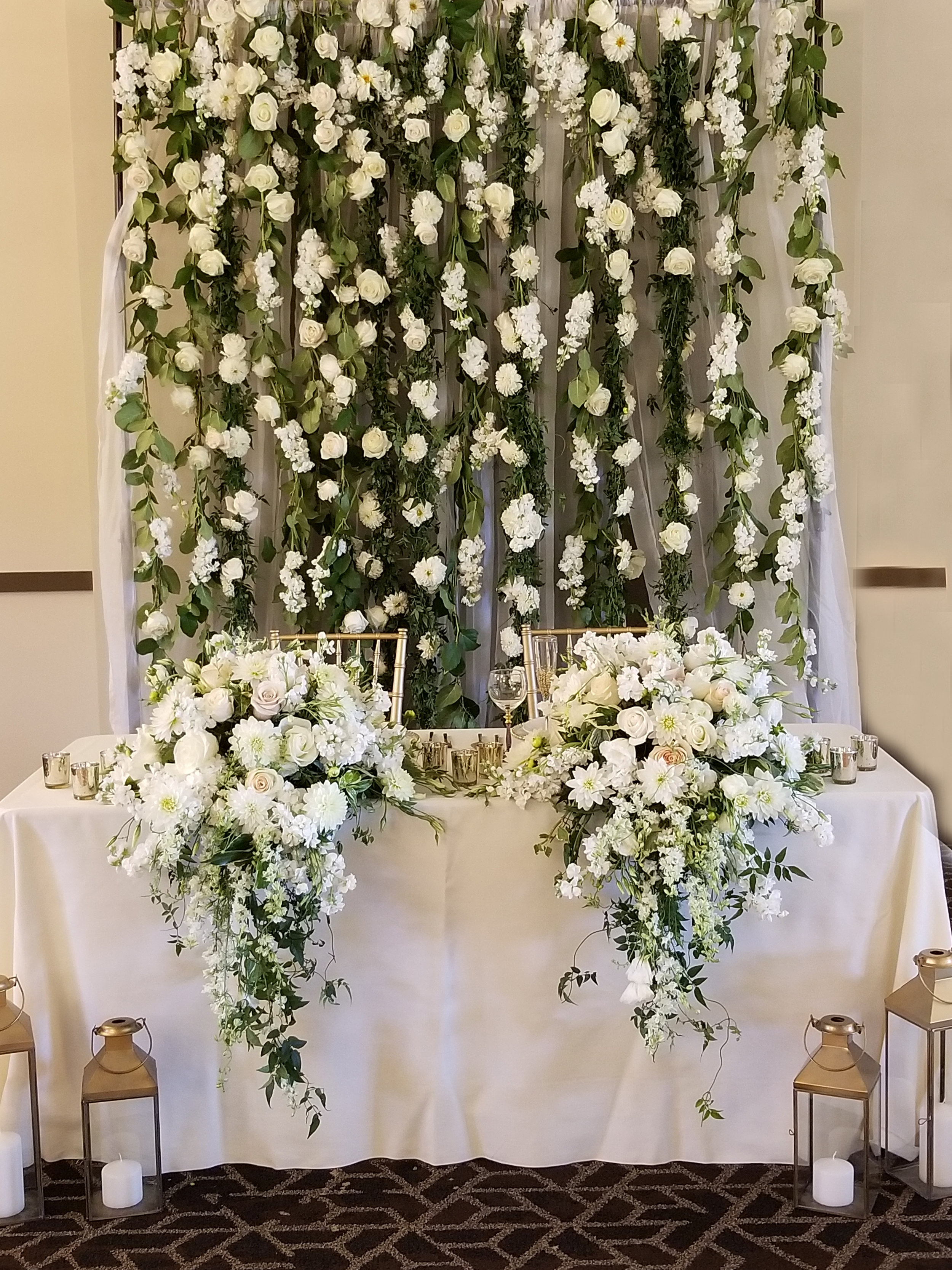 Sweetheart table floral wall, hanging passion vines and lush white flowers. Sweetheart table cascade florals draping off the table.