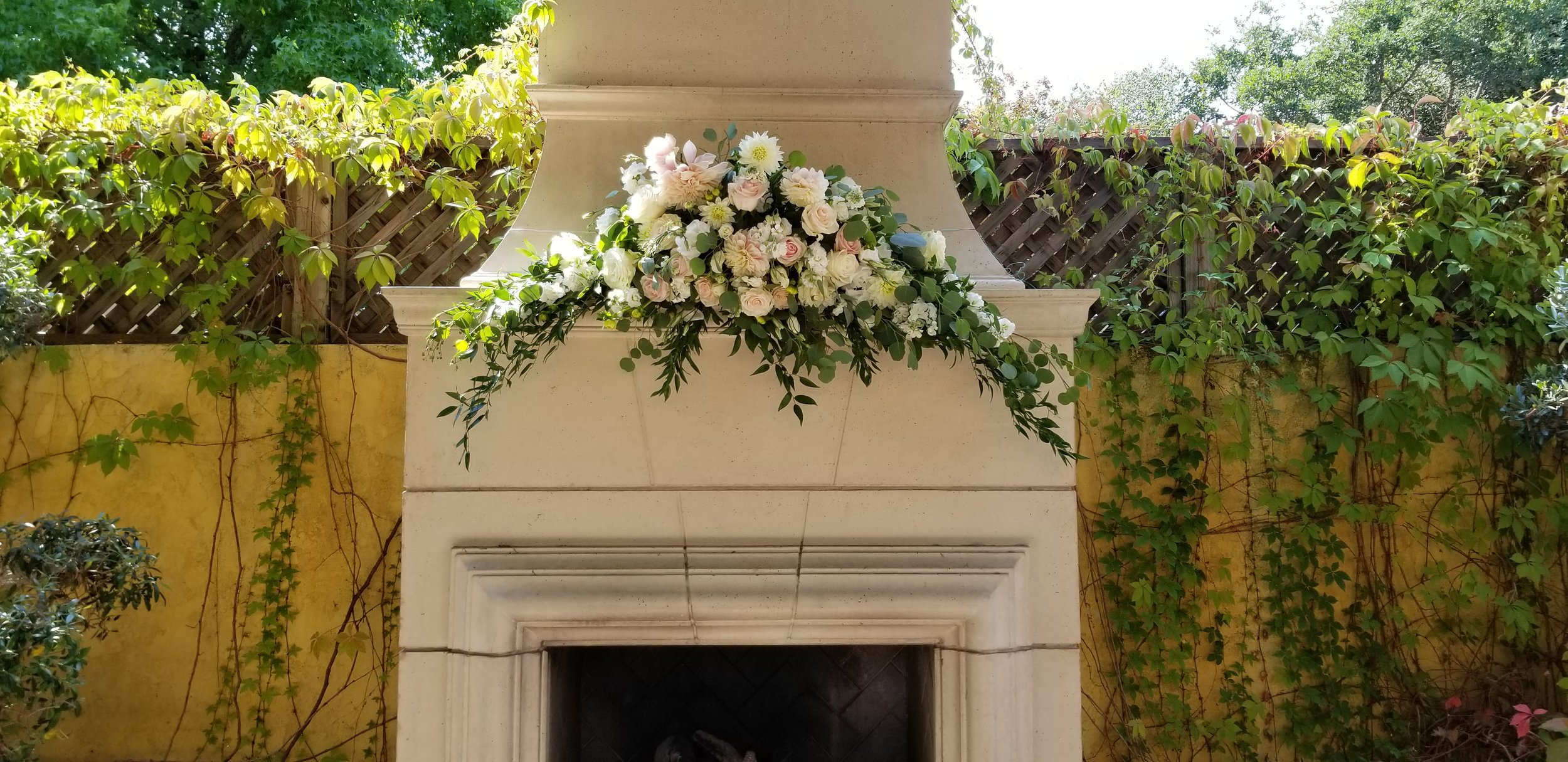 Outdoor fireplace wedding ceremony at Depot Hotel in Sonoma. Floral display on mantle includes shades of white and blush flowers and flowing eucalyptus greens