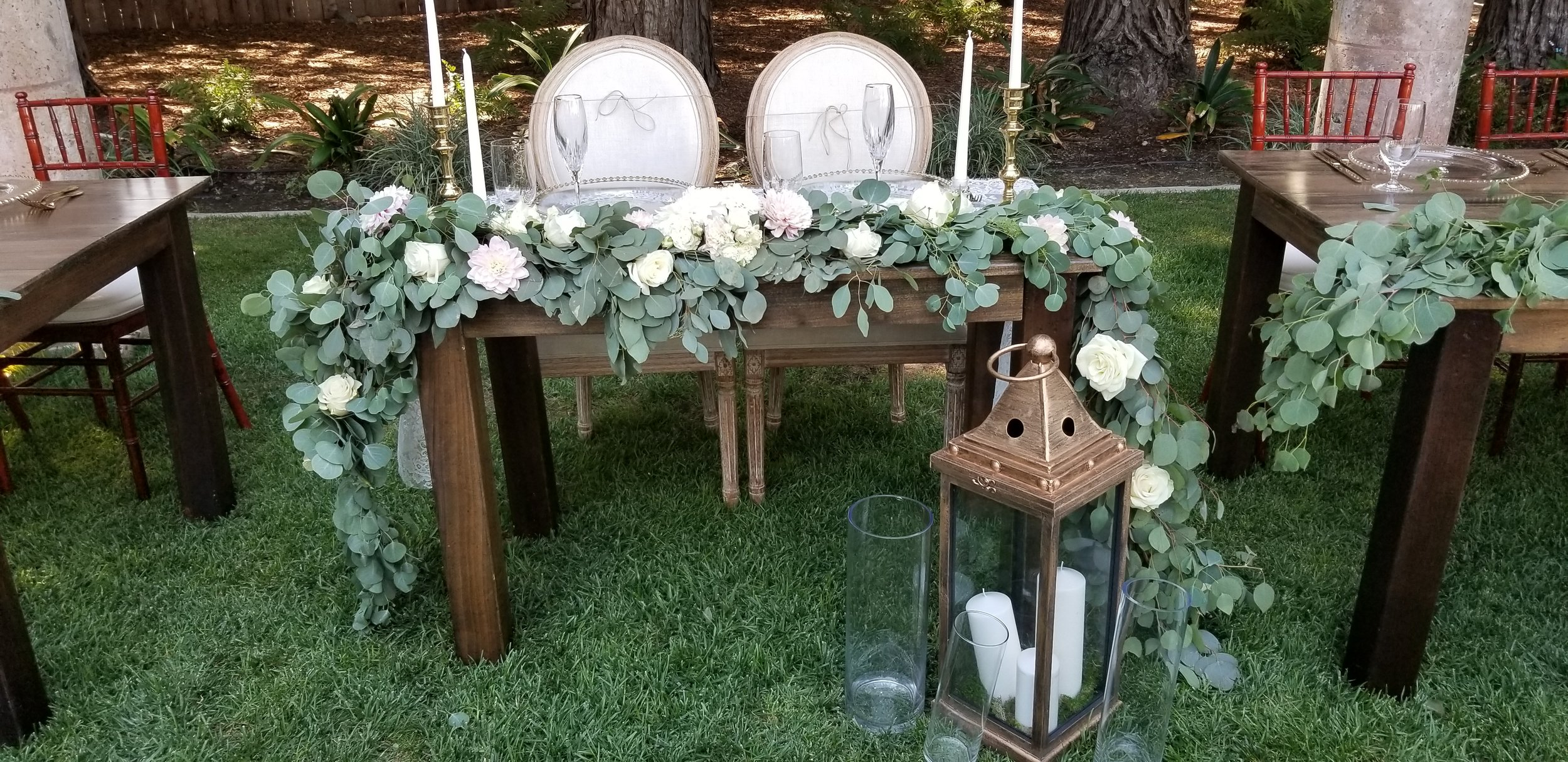 Sweetheart table garland in lush green eucalyptus and white roses and dahlia. Trentadue winery.