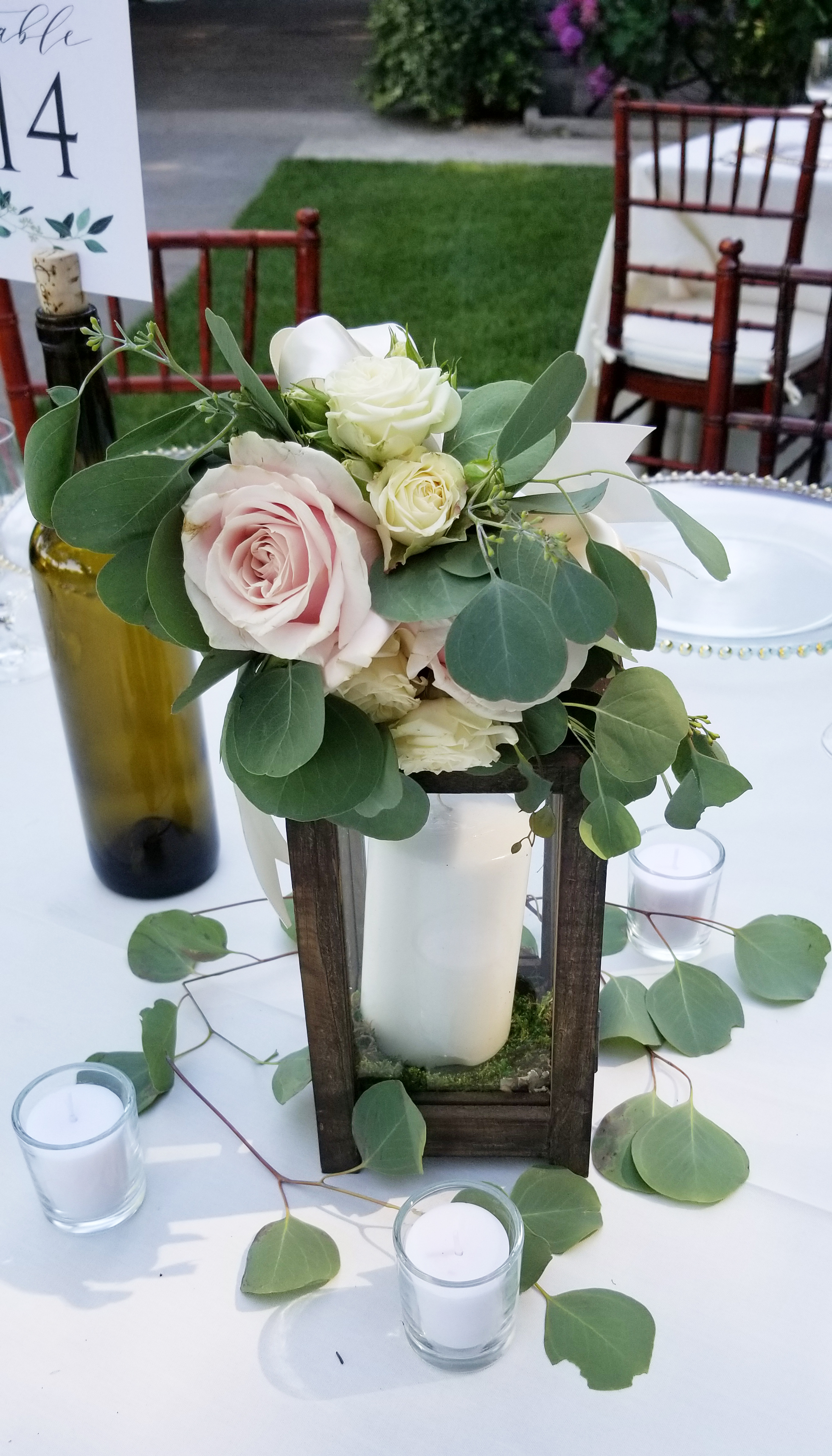 Centerpiece lantern with floral, small clutch of flowers and greens tied to the top of the lantern.