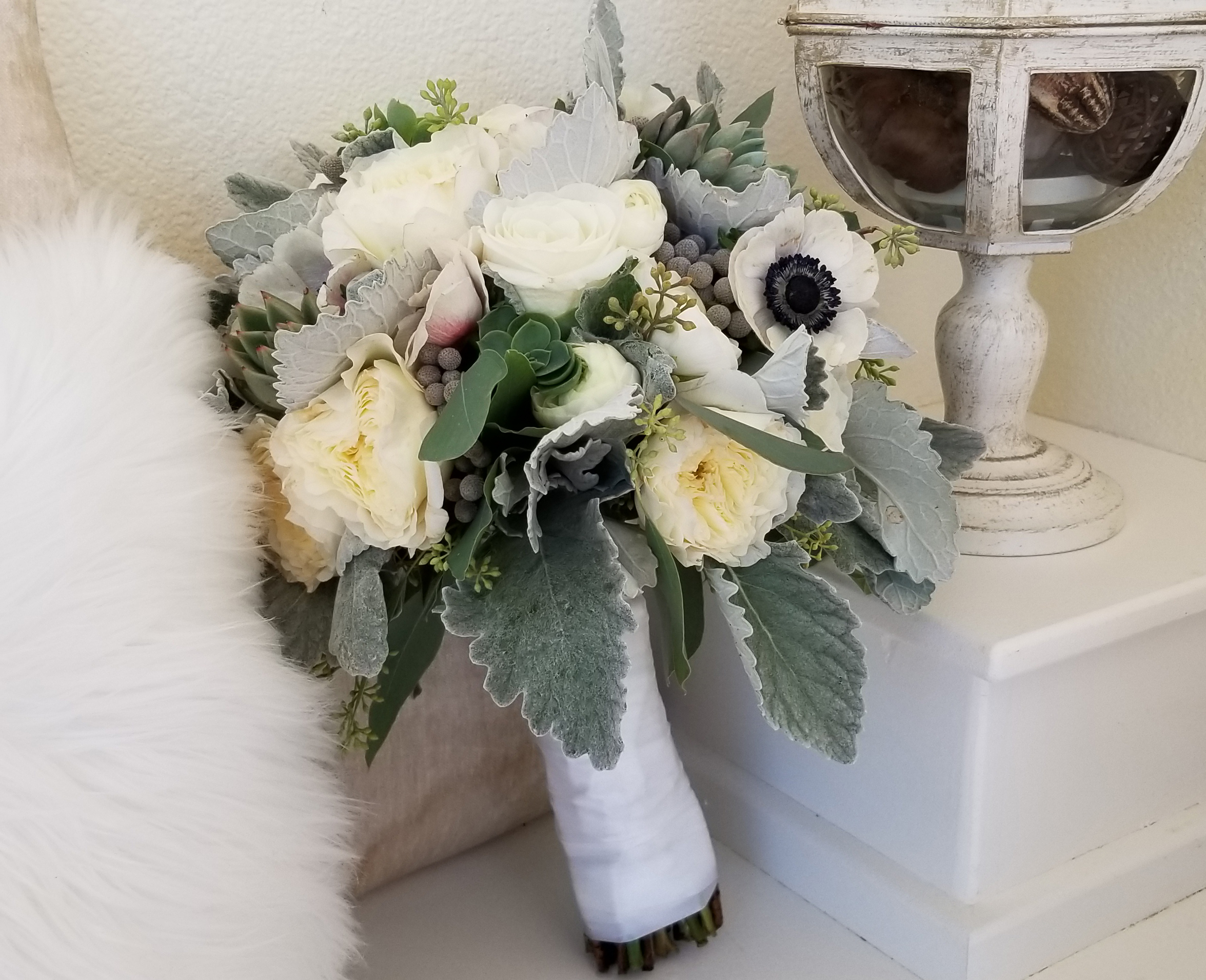 Romantic white and gray bridal bouquet, flowers include anemone, garden roses, succulents, ranunculus, brunia balls and dusty miller.