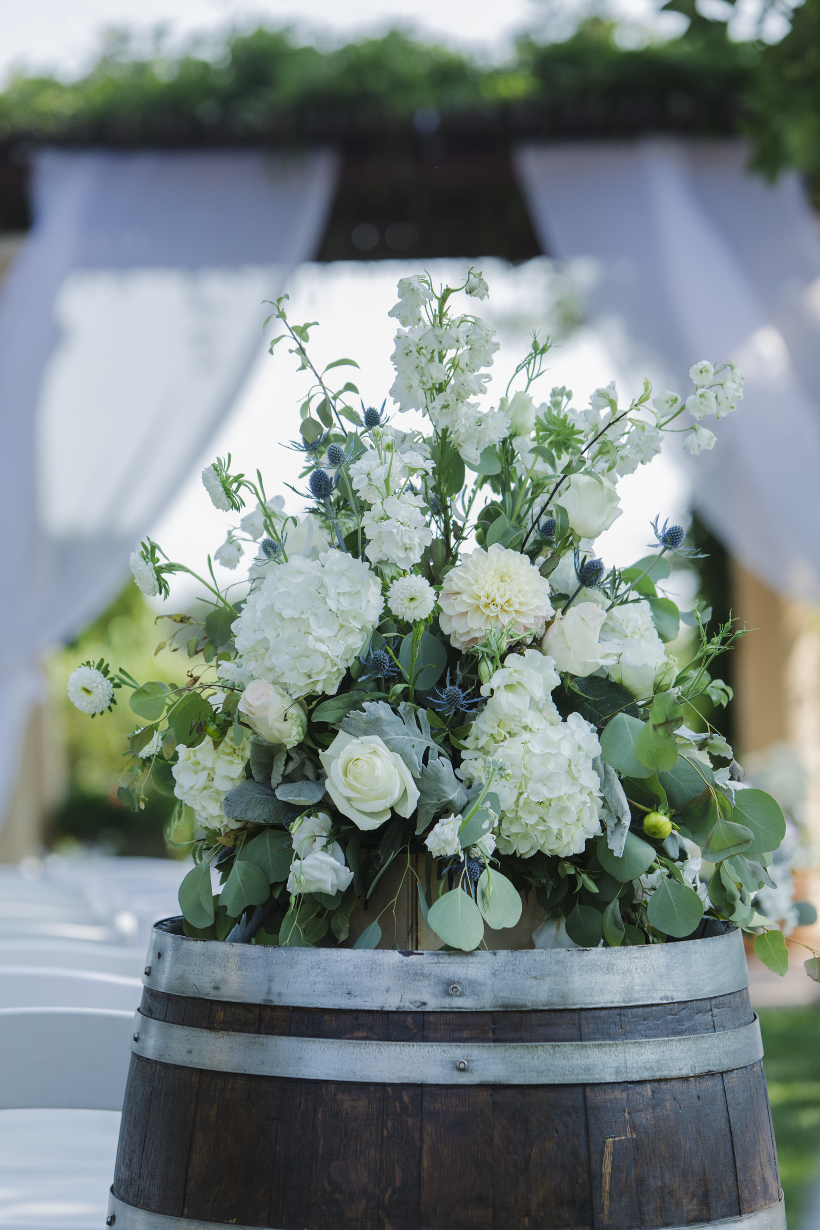 Wine barrel topped with lush white hydrangea, roses and stock, eucalyptus greens. Vintner's Inn wedding ceremony