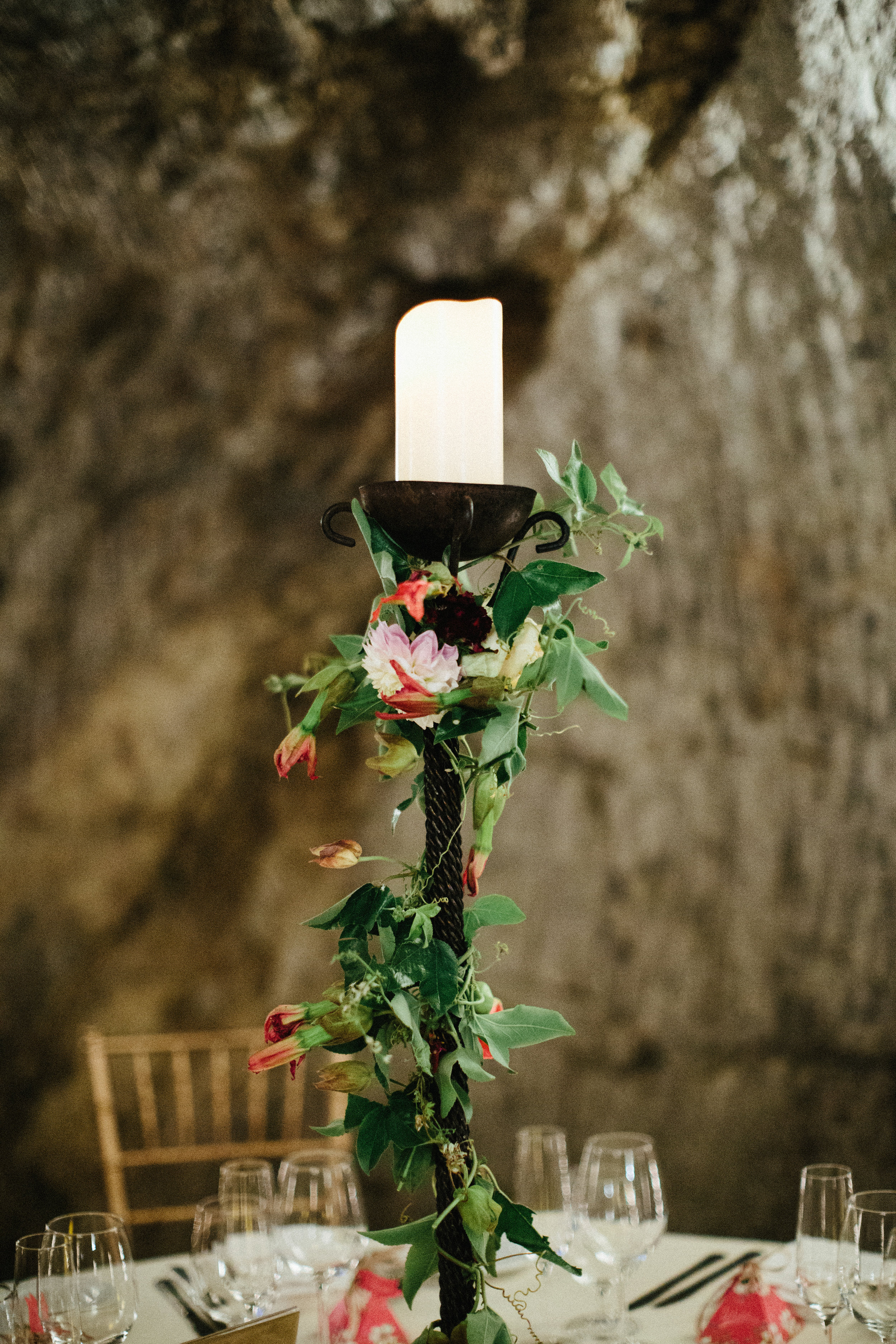 Hans Fahden wine cave reception, candelabra decorated with greenery and vivid passion flowers and roses.