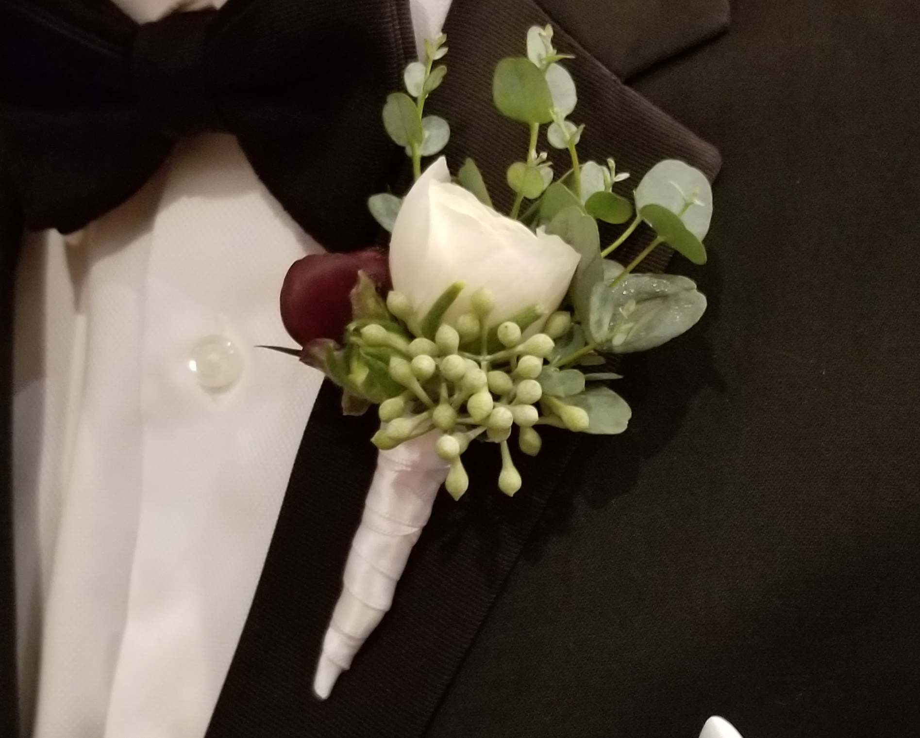 Groom's boutonniere, white ranunculus with spray of burgundy and seeded eucalyptus.