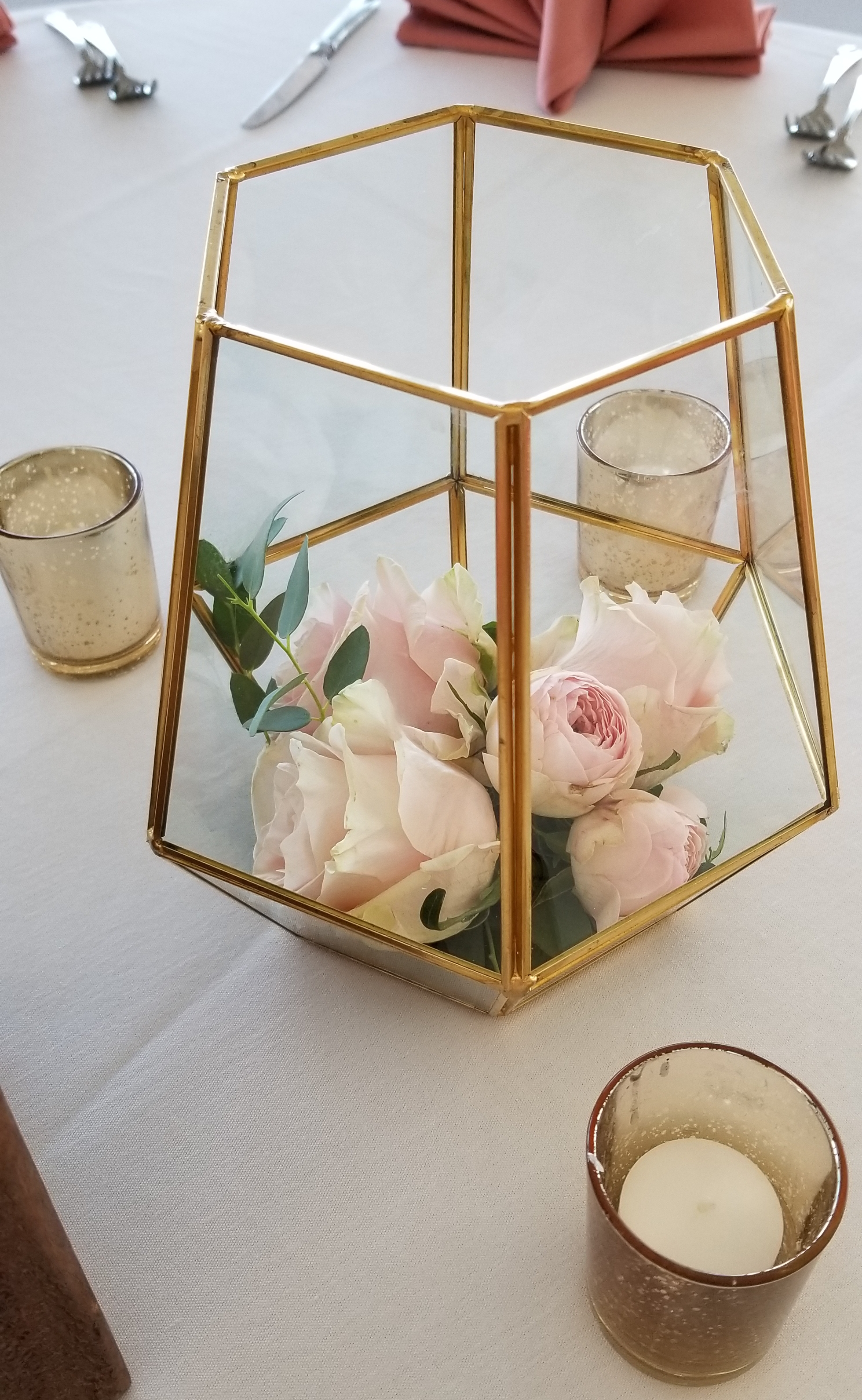 Clear terrarium centerpiece with blush pink flowers  featuring ranunculus and garden roses, and a sprig of greenery surrounded by gold mercury candles. Eagle Vines Golf Club.