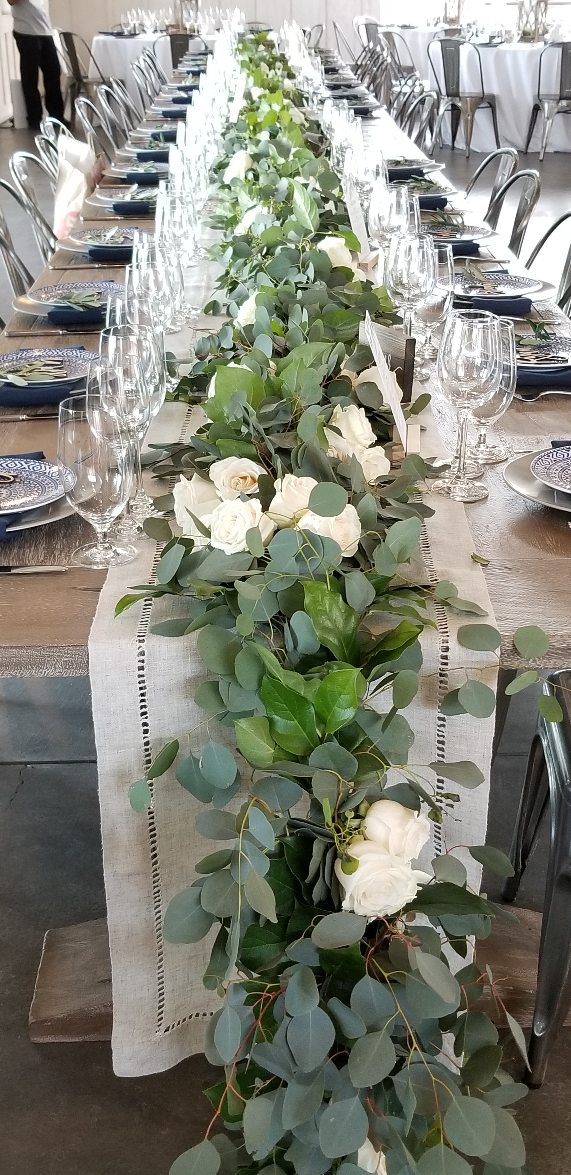Long farm table lined with a fresh eucalyptus runner, laced with fresh garden roses. Perfect Sonoma wine country wedding reception.