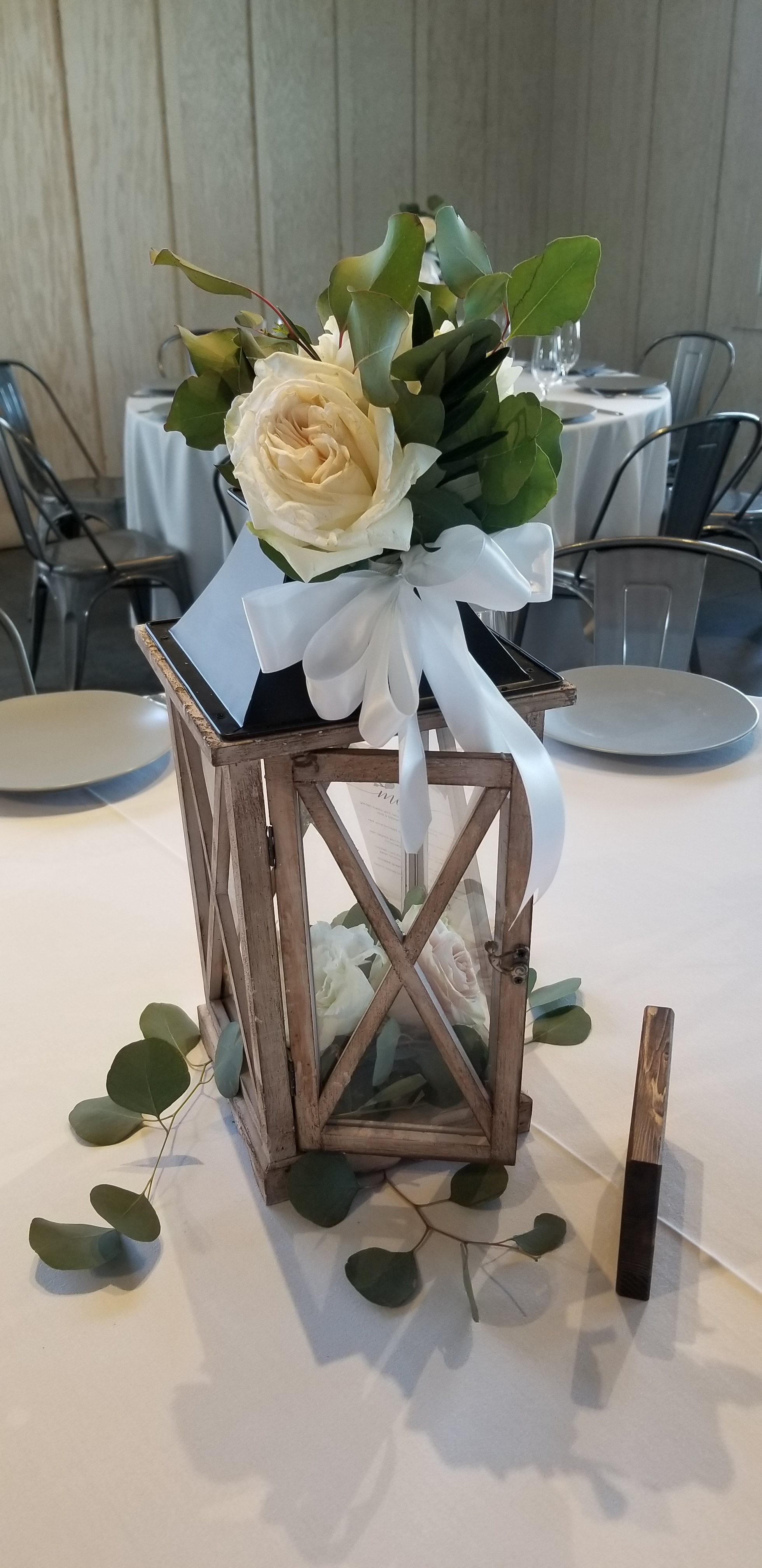 Wedding centerpiece, rustic lantern adorned with fresh flowers and greenery.