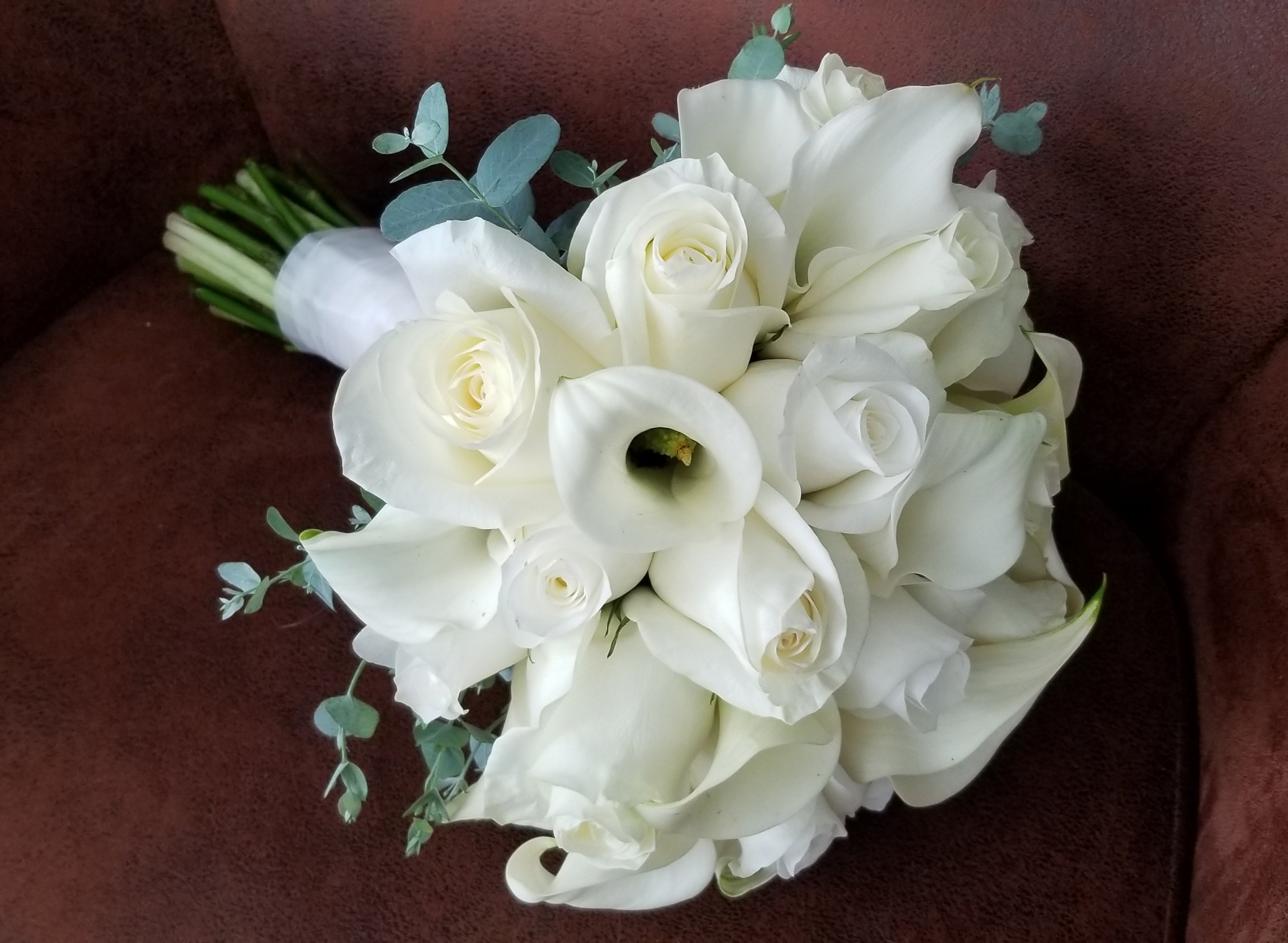Pure white bridal bouquet featuring white roses and white calla lilies, just a hint of eucalyptus greenery