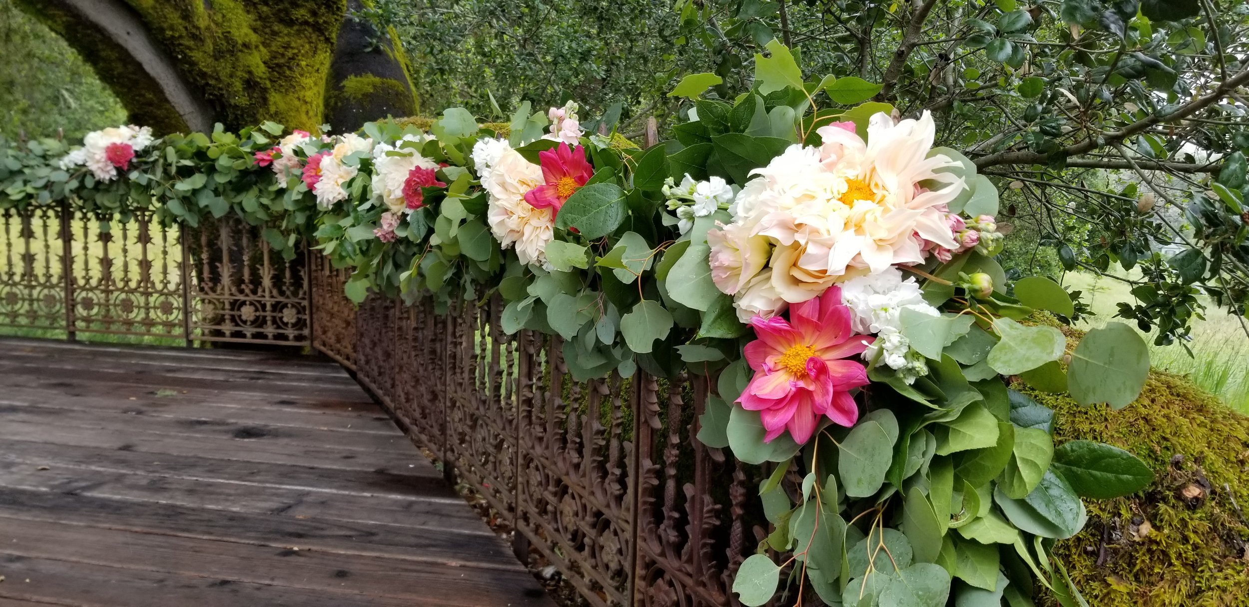 Wedding ceremony garland at Mountain House Estate in Cloverdale. Lush eucalyptus greenery, bright pops of colorful flowers line the fence line for a wine country wedding ceremony