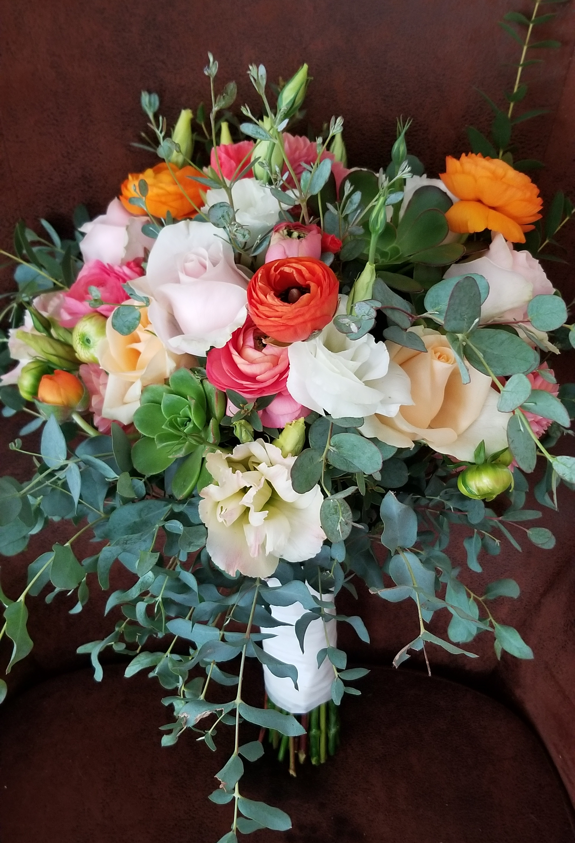 Bridal bouquet, loose leafy greens with pops of coral, gold and blush ranunculus, dahlia, garden rose.