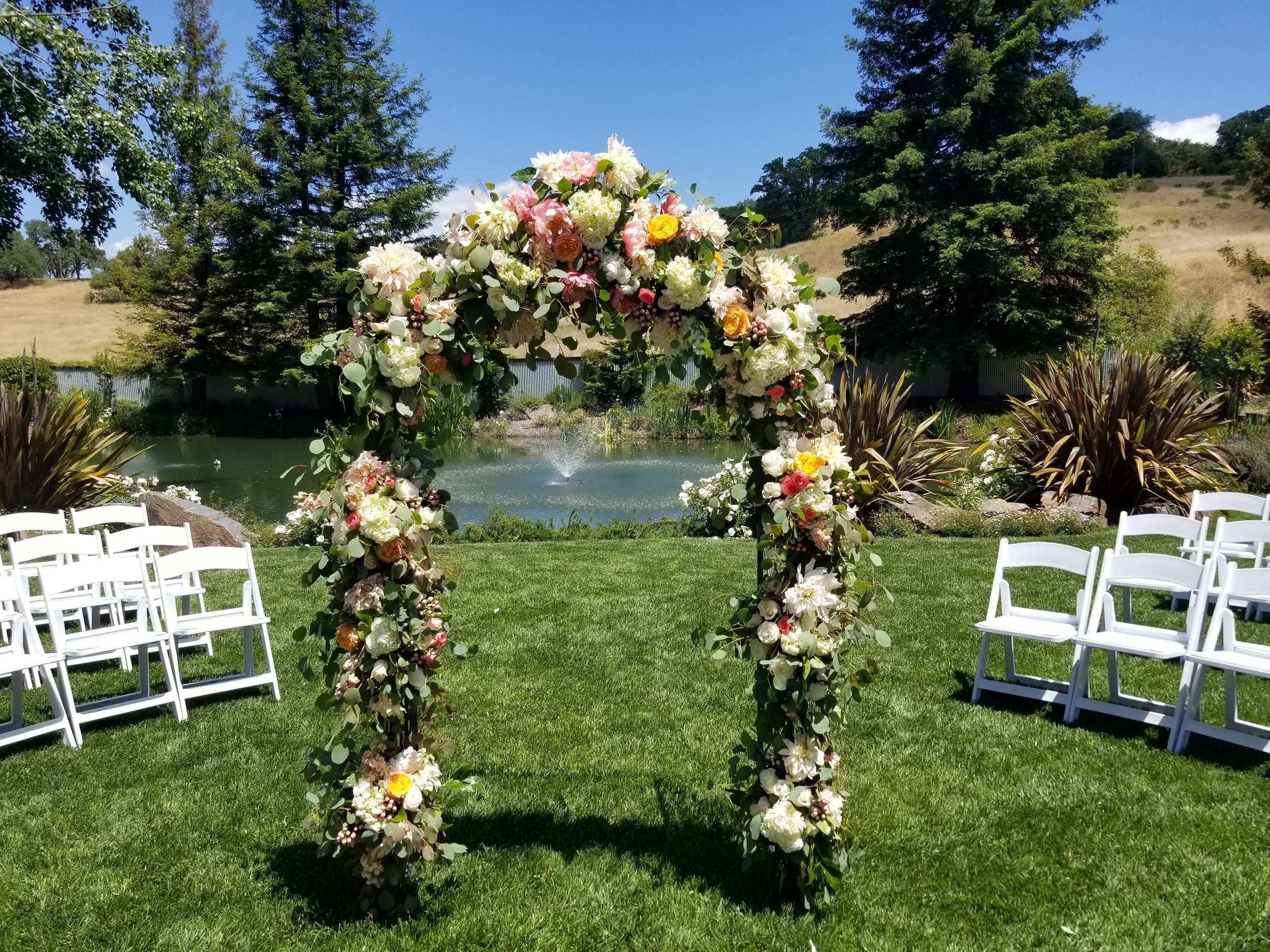 Wedding ceremony arch loaded with fresh summer flowers and eucalyptus greenery. Mountain House Estate wedding by the pond.