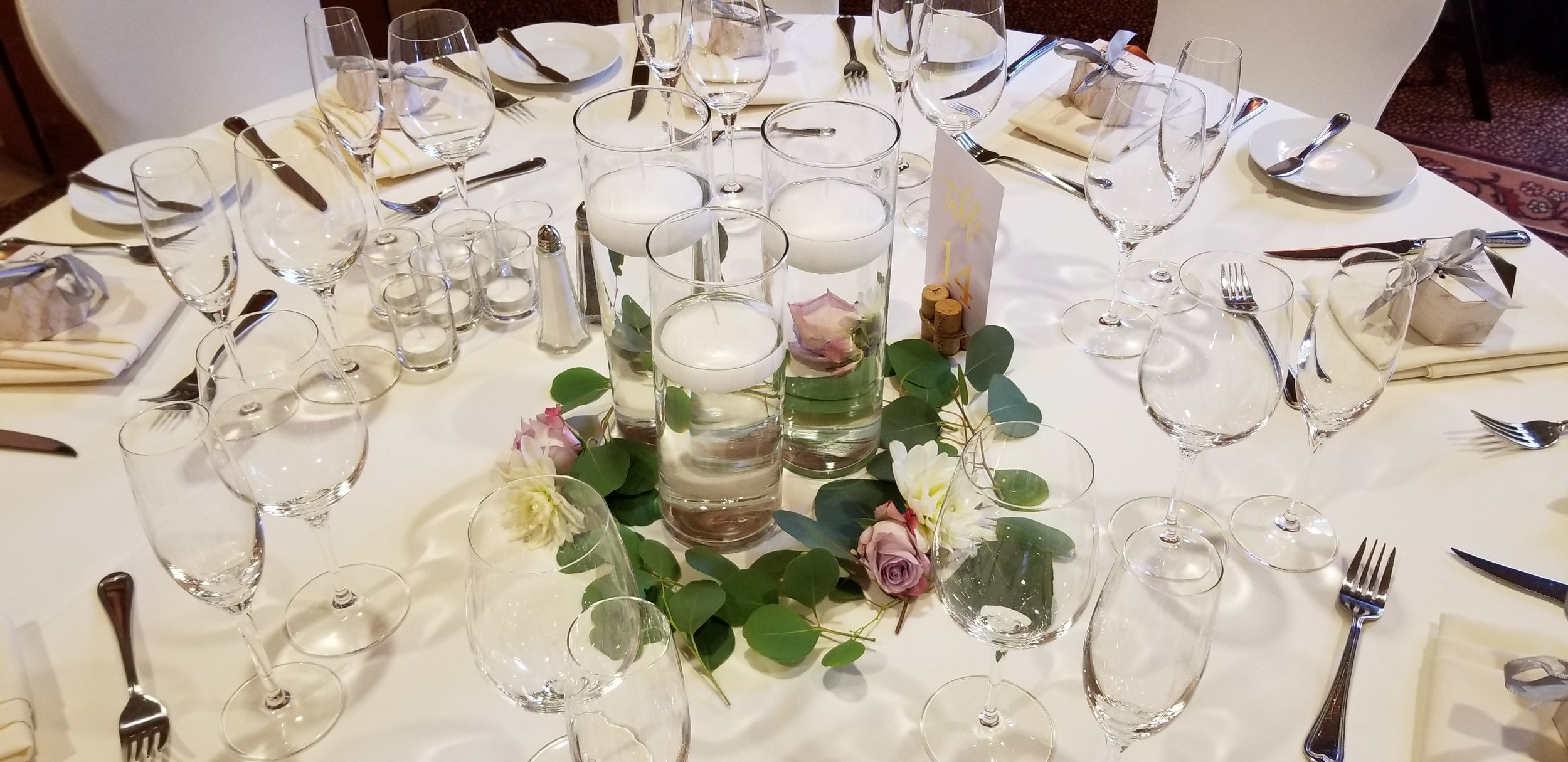 Trio of glass pillars with floating candles and greenery base