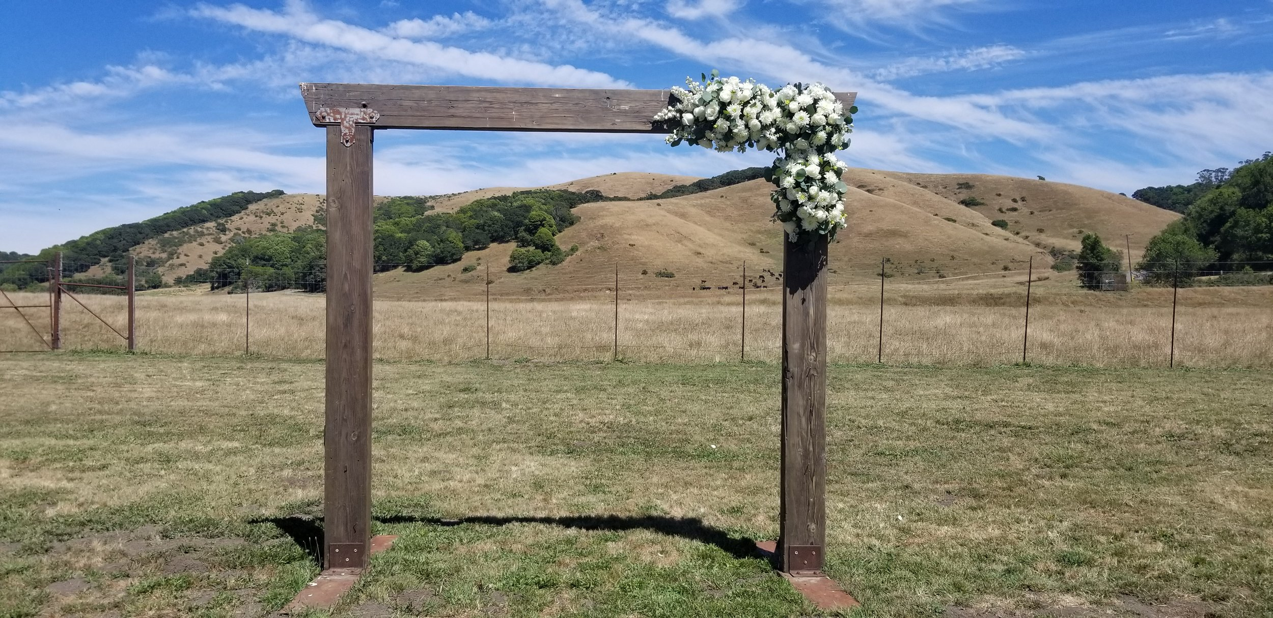Rustic ranch arbor at Rosewood Events, Petaluma. Pure white floral with eucalyptus greens