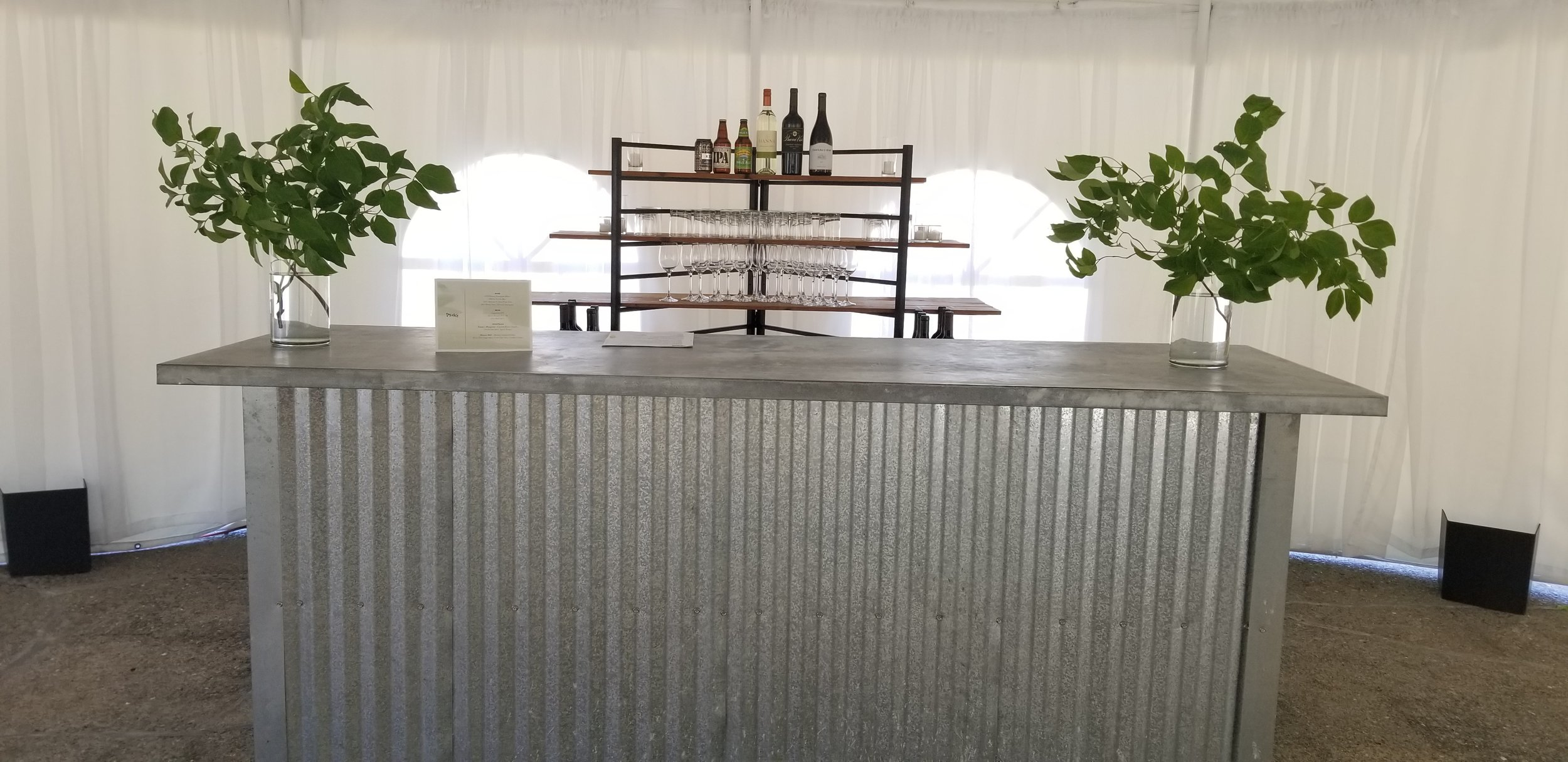 Rustic country tin bar featuring the simplicity of dogwood branches placed in clear glass urns.